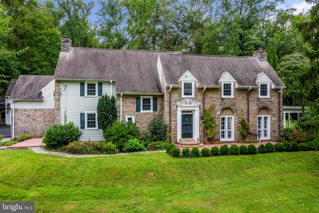 """Situated in one of the most prestigious areas of the Main Line sits this classic 2-story colonial.  This Radnor Township neighborhood was named """"Rittenhouse Arbor"""" many years ago because of the luscious trees, tranquil setting, and the serenity that it offers. Close to the heart of Wayne and Bryn Mawr yet far enough away to enjoy the peacefulness. This gracious home was built in 1932.  The entrance hall sets the stage for the glory of its past, which is enhanced by an Inglenook-like room that includes a brick fireplace, built-in bookcases, and French doors opening to the patio. Step down to the formal living room, which offers built-in bookcases a brick fireplace, as well as 5 sets of French doors to the front and back patios. A lovely fishpond with fountain is located in the corner off the terrace. The large dining room, perfect for large family gatherings, offers a third fireplace, lovely built-in shelving for your china, and access to the side yard.  The beautiful bright gourmet kitchen and breakfast room is complete with a powder room, butler pantry, and is open to a light-filled filled family room complete with comfy radiant heated floors. Exit from the kitchen to the beautifully landscaped yard with an inviting pool and patio. The second floor offers 5 bedrooms, 3 full baths, and a 1/2 bath. The fifth bedroom has its own private bath and is the perfect arrangement for a Nanny or guests.  A laundry closet is located on this level. A bonus is having a back staircase to the kitchen. The floored attic offers easy access for storage.   The detached 2 car garage features a large finished second floor with a full bath.  It can be used as an office, nanny suite, or guest room. This gorgeous home is complete with Hardwood floors throughout, professionally landscaped gardens, a gorgeous kidney-shaped pool, and a hot tub that will be included.  The entire home has recently been freshly painted.  This is the perfect location for dining, shopping, or walking the 5-mile Rad"""