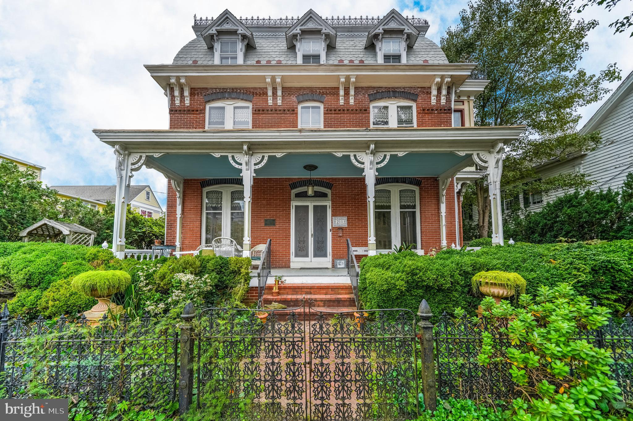 """Own a piece of history, in the Heart of Middletown's Historic District Proper, with this stunning Victorian French Second Empire with Italianate Windows property dating back to the early 1880's. 211 N. Cass Street is on the National Register of Historic Places of the United States Department of the Interior. Being just steps from Governor Bigg?s Mansion, this property exudes historic charm, but with today's modern conveniences - truly the best of both worlds and MOVE-IN READY! This grand Victorian is of solid brick construction (with added brick embellishments) and a slate Mansard roof to enhance the charm. The charming period cast iron fence perfectly compliments the landscaping and brick walkway with stunning blooming perennials. The main roof line (and two side bay window roofs) also contain increasingly rare intact cast iron cresting. The back yard is enhanced with a semi-circular brick patio and Koi pond overlooking the serene lot where landscaping opportunities are endless. The large front porch with standing seam metal roof, welcomes you back into a piece of history. Upon entering the foyer, you'll immediately notice the stunning hardwood flooring, custom and unique doors, detailed oak fretwork and original Eastlake hardware - all which can be enjoyed throughout the home. On one side of the foyer you'll find a large formal living room with a Harman palladian-windowed wood pellet stove & period chandeliers with plaster medallions.  On the other side you enter the formal dining room through the curved double doors featuring a wedding cake crystal chandelier. Throughout the home there is many hand painted and stained glass period windows. Past the foyer is the inviting kitchen. The kitchen, updated in 2019, features dovetailed natural maple/glazed cabinets, stainless steel appliances and granite counters. Conveniently located off the kitchen, in an adorable """"mudroom"""", which includes a washer + dryer and pantry area. Behind the kitchen is a large family room addi"""