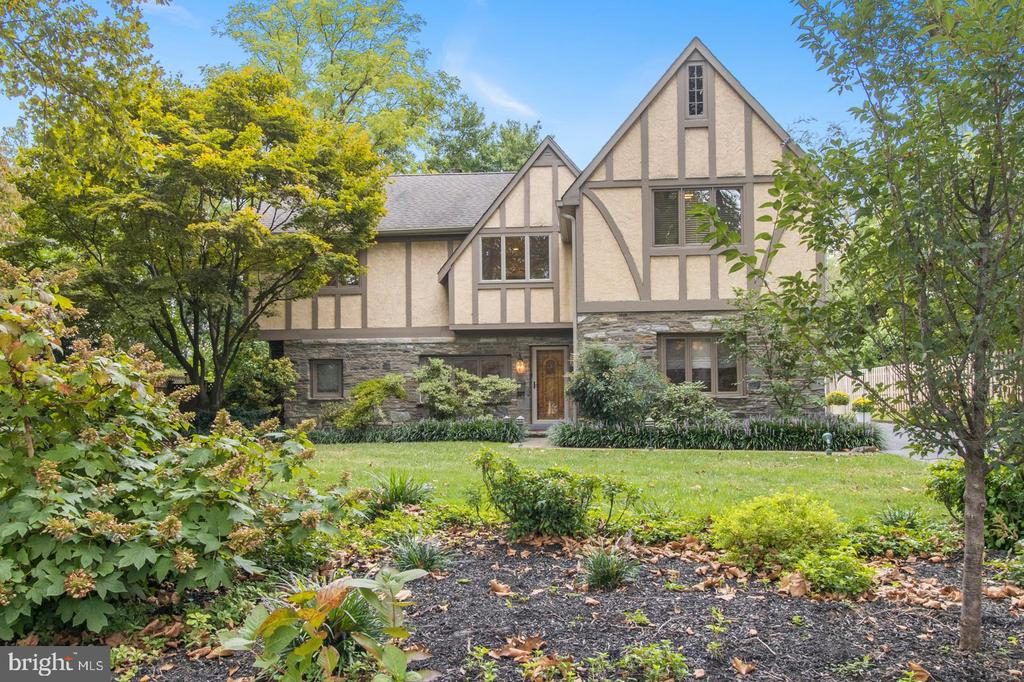 Located in one of the most coveted neighborhoods in Wynnewood, this is the Lower Merion home that you have been waiting for! Immaculately maintained and thoughtfully upgraded, this beautiful Tudor style home was completely rebuilt in 1988 on the original 1940's stone foundation. Its unique floor plan provides over 3500 square feet of flexible living space. Enter the home into a two-story formal foyer with inlayed wood floors, custom cabinetry, and a powder room. Just beyond is the spacious living room with built-in bookcases and a double sided fireplace shared with the comfortable family room. The family room has a  large hardwired television and  lots of custom built-in bookcases, providing a wonderful gathering space for tv watching or relaxation. Also off of the foyer is the formal dining room which could alternately be used as an office for those who are working from home. The kitchen was thoughtfully updated with beautiful solid cherry cabinets, granite countertops, and stainless appliances. Adjacent to the kitchen is a sitting room which would make a great homework area, playroom or reading nook. A light-filled gallery opens to the oversized deck and beautifully landscaped fenced-in yard. On the second floor you will find the spacious primary bedroom which has vaulted ceilings, a private balcony, two walk-in closets, and an oversized en-suite bathroom. Three additional good-sized bedrooms and a hall bath are just off the second floor landing. Continuing down the hallway, you will find another bedroom, full bath, laundry room and a large light-filled bonus room that has soaring ceilings and a Palladian window that overlooks the back yard. This area is accessible from a private outdoor entrance, and would be great for and au-pair suite or a multi-generational household. The home is fabulously located within walking distance of schools, South Ardmore Park, the JCC, houses of worship, public transportation, and all of the restaurants and shops in Wynnewood. Schedule your showing today. This beauty will not last!