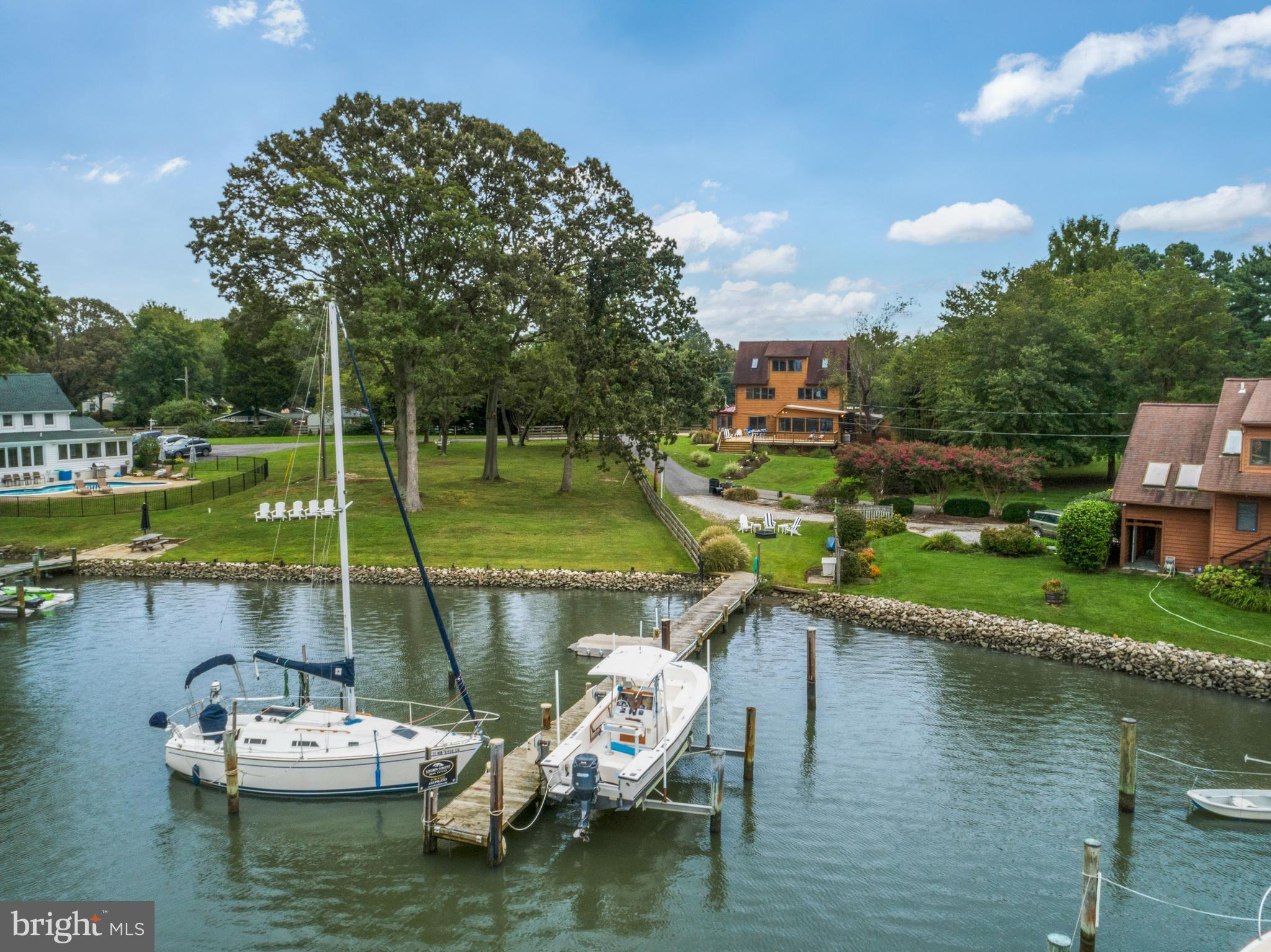 EDGEWATER WATERFRONT on .72 acres!!  Breathtaking sunset views await you at this prime waterfront property located on a private lane of million-dollar waterfront homes.  Water views fill this sunny home on three levels.  The living room and kitchen-sun room walk out to a huge deck overlooking the water.  The kitchen has gorgeous quartz countertops including an 8-foot island with seating.  The kitchen flows into the adjoining sunroom for relaxed dining or sitting. The living room is light and bright with white painted beams for a modern, coastal vibe.  Decorator-selected neutral creams and greys have been used in the beautiful updated flooring and freshly painted walls.  There is a spacious main level guest bedroom and full bathroom.  Also on the main level is a library-study area and a large game-rec-TV room with access to the backyard and garage, as well as the laundry room with added storage. Lots and lots of windows bring in natural light to the 2nd floor which is home to the master bedroom suite with bath, and a large open area currently used for a home business office, plus an additional bedroom. Huge master bedroom with his and her (walk-in) closets and a balcony that overlooks the water and has stairs leading down to the private backyard.  Third floor has 2 bedrooms, full bath, and a common area between, with spectacular water views that could accommodate another sleeping area or would be a great hang-out room. This property also boasts multiple outdoor living spaces.  In addition to  the massive deck space, enjoy relaxing in privacy in the hot tub in the screened porch or sunbathe on the patio in the fenced back yard; or make use of the huge fenced side yard for more active recreation or birdwatching the overlooking cove. This is a fantastic location for boating whether you like to sail or fish or just paddle board.  You can dock your sailboat (4.5 ft water depth) and power boat (10,000lb boat lift) and other water toys at the pier located on the protected w