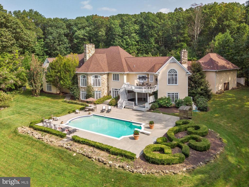 Absolutely phenomenal custom masterpiece nestled on a private 6.64 sprawling acres offering everything you could possibly desire! Amazing private tree-lined driveway, new roof (2019), inviting courtyard, koi pond, oversized three car detached garage with additional lower level storage, covered breezeway, stately columns, gracious covered porch complimented with triple French doors, in-ground pool, tiered Trex deck, and professionally landscaped grounds! Step inside to find no expense spared boasting over 10,000 finished square feet, spectacular hardwood floors, sunbathed windows, soaring domed ceilings, four fireplaces, three zoned HVAC, open concept, sophisticated style, detail, and design! The captivating main level features a gorgeous entry foyer highlighting hardwood floors and an intricate vaulted ceiling. Continue into the elegant great room embellished with a domed ceiling, light-filled lofty windows, and a decorative marble profile gas burning fireplace. Entertain in the formal dining room graced with medallion molding and a remarkable crystal chandelier. Prepare chef-inspired meals in the custom kitchen outfitted with professional-grade appliances, granite counters, prep sink, gas cooking range, sleek tile backsplash, planning station, wine refrigerator, center-island, trash compactor, and a breakfast bar. The adjacent family room provides the ideal place to enjoy movie night featuring a stacked stone wood-burning fireplace, two ceiling fans, and deck access! Retire to the main level owner's suite adorned with a gas burning fireplace, ceiling fan, and a private balcony with French doors. Relax and unwind in the en suite bath bestowing separate vanities, Jacuzzi, large open shower, bidet, and a magnificent custom walk-in closet. Two sizable bedrooms, dual entry bath, powder room, and a home office complete the designed inspired main level. The excitement doesn't end on the main level; the above grade fully finished lower level presents a second kitchen enhanced with granite counters, breakfast bar, gas cooking, and pendant lighting. Two vastly sized bedrooms with walk-in closets one with an en suite bath boasting a Jacuzzi and separate shower (perfect in-law suite), a second family room, game room, exercise room, and a powder room conclude this mesmerizing estate. After a long day enjoy the sunrise and set from the comfort of the tiered deck overlooking the outdoor oasis, in-ground pool, and total privacy! Welcome to the embodiment of Maryland's good life, it just doesn't get any better than this!