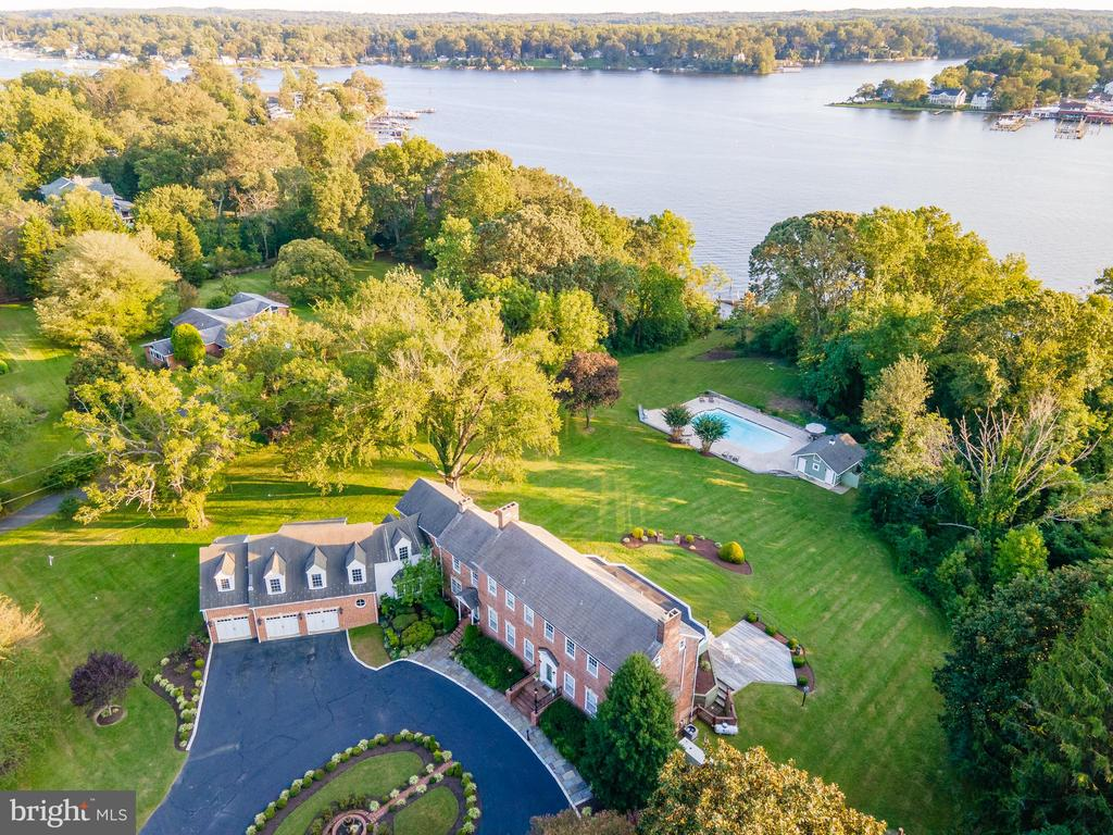 """""""Olde Bloomfield"""" plantation, located in the heart of Annapolis, is prominently positioned on a 3+ acre bluff overlooking the South River.  This waterfront estate has been lovingly remodeled to maintain the best features of the original Federal period home while incorporating numerous modern amenities.   Guests are greeted by the boxwood lined circular arrival court which features a beautiful central fountain and a three-car garage.  This property offers the complete waterfront package complete with a 25' x 55' waterside pool, pool house, deep water pier, tree-lined private lawn and over 80 feet of waterfrontage.  This plantation was once part of a late 17th century land grant known as """"Brampton."""" Historians believe that prominent Annapolitan Allen Quynn, who purchased Brampton in 1791, built the home around the turn of the century.  The Federal style architecture includes exterior detailing such as bricks laid in the Flemish bond style, stone lintels decorated with a key-block, and dentil molding.  The current owners built an appropriately-scaled addition, designed by renowned architect Cathy Cherry, that updated the home with a family room, two bedroom suites, and the three-car garage.  The older part of the home included a formal living room, dining room, sunroom, kitchen and three bedrooms/four bathrooms.  With the addition, some space was re-configured to create an upstairs laundry room, additional walk-in closet, powder room & dedicated dog shower.  The lower level has an exercise room, 2nd laundry room, and lots of storage.  Just across the waterside lawn is the large pool, with plenty of decking and a custom outdoor kitchen for optimal entertaining.  There's also a pool house with changing rooms. The private pier with 5ft water depth is perfect for the boating enthusiast plus this setting provides quick access by boat to the nearby waterfront restaurants and the Chesapeake Bay.  Conveniently located to access Downtown Annapolis, head over the Bay Bridge to t"""
