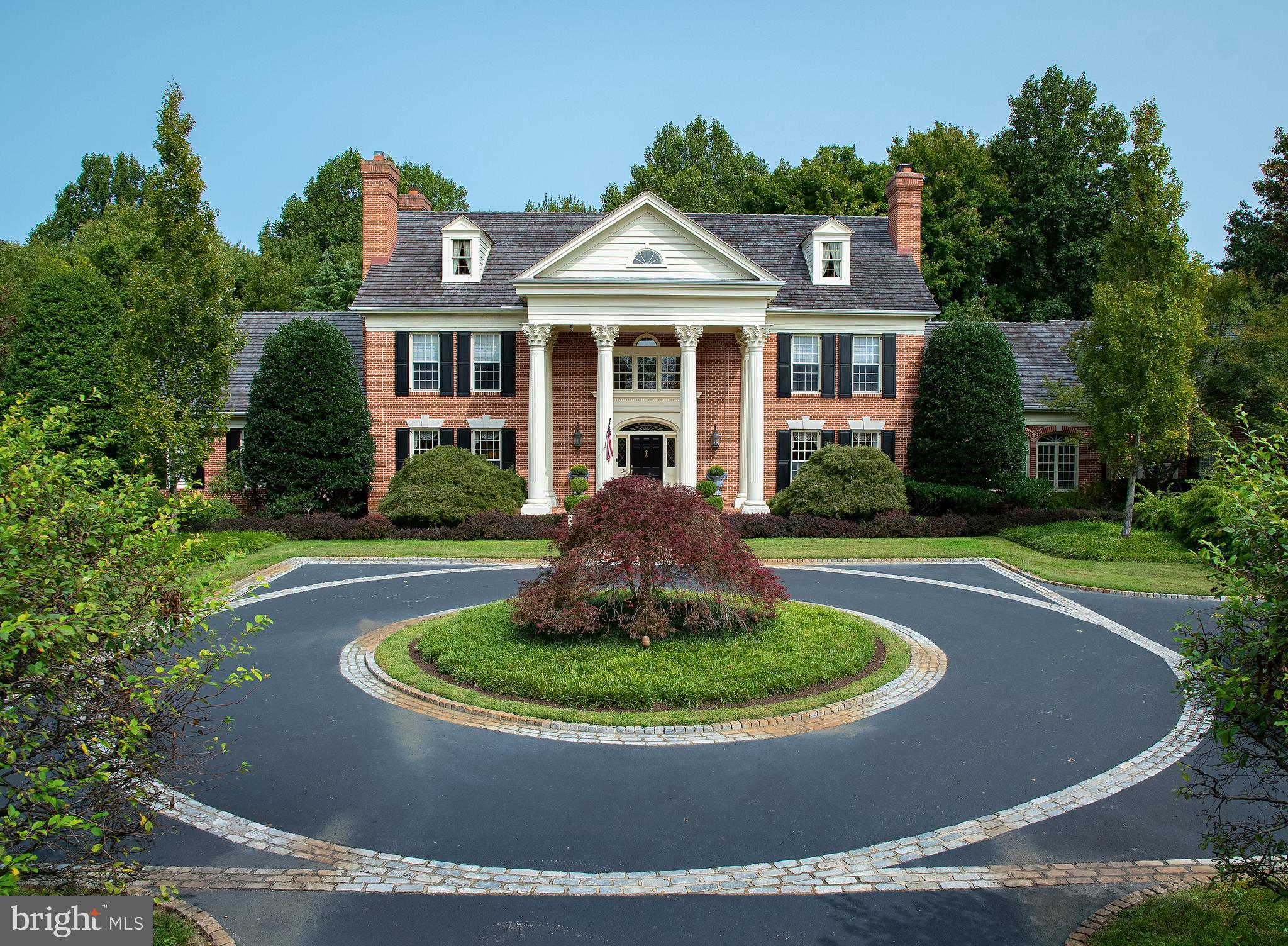 """This magnificent brick home, with its distinctive Georgian architecture designed by Ann Capron, welcomes the visitor with its circular drive, gated entry, and Gale Nurseries-award winning and beautifully landscaped, 5.4-acre grounds in the heart of Willistown. With 5 bedrooms, 7 full baths and 2 powder rooms, and 6 fireplaces, this homes fortress-like features include concrete walls and double dry walls for sound reduction, 9- to 12-foot ceilings throughout, impressive millwork and wood floors. The stunning Hunt Room, home theater, gorgeous outdoor pool, and 3,200-bottle wine cellar are just a few of its overflowing amenities. With more than 12,000 square footage and building materials that in today's dollars would exceed $5 million, 853 Providence Road is truly one of a kind. A soaring, two-story foyer welcomes you into expansive living spaces with graceful touches including 4-layer custom moldings, arched doorways, and beautiful fireplaces. The first level features a formal living room and dining room, chefs quality kitchen and adjoining dining area, sunroom with 12-foot coffered ceilings, and a truly unique hunt room with 20-foot beamed ceilings. The first floor also has a main suite with bed and bath, home office, two lovely powder rooms, and large laundry. On the second level, there is an in-law/guest suite above the garage, as well as three generously sized bedrooms, each with their own en-suite bath. A walk-up, floored attic provides an additional 2,000+ square feet, convertible to living space. With two floors of formal, traditional rooms, the Garden Level offers true, eye-catching flair, with oak flooring, French-style café, and hidden second entrance to the """"ancient"""" wine cellar. This level has a second full kitchen for easy entertaining (the level leads directly to the patio and pool). You'll also find a billiards room with a 25-foot granite-top bar with brass foot rail, and a host of special antiques, including a phone booth with working phone and a Post"""