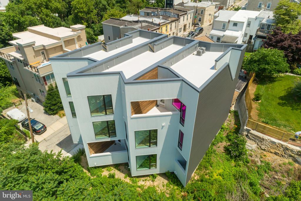 Welcome to Mountain House - A special collection of 3 ultra contemporary townhouses nestled in the hills of Manayunk. Designed by award-winning architect, ISA, and built by local custom builder, United Makers, these 3 BR/2.5 BA homes feature architectural design with dramatic angles, high ceilings, floor to ceiling windows throughout, several outdoor balconies and a fabulous rooftop deck. Ascend from the entry foyer to an open-concept living floor ideal for today's lifestyle. The sunken living room with high ceilings, floor to ceiling windows and step-out balcony is flooded with natural light giving the house a light and airy feel. The open chef's eat-in kitchen features white and wood contemporary flat-panel cabinetry, stainless steel appliances and calacatta quartz countertops and island. Dining area with floor to ceiling windows plus powder room complete this floor. The dramatic open riser staircase leads up to the Master floor oasis. Fabulous Master BR with floor to ceiling windows, step-out balcony with westerns views, dual closets plus en-suite bathroom with step-in shower with frameless glass doors, contemporary double vanity plus separate water closet with pocket door. Down the hall is an office/sitting room with yet more floor to ceiling windows. Third floor offers 2 great-sized guest BR's, hall BA plus a convenient laundry closet with washer/dryer. Access to the rooftop deck with spectacular sunset views. 1-car attached garage. 10 year property tax abatement. Easy walk to Main Street and the train. Convenient to Center City, the suburbs and major highways. Truly exceptional and unique homes in desirable Manyunk location.