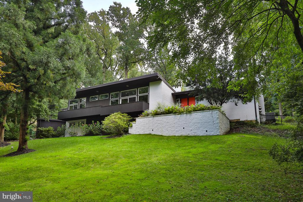 This true Mid-Century Modern raised ranch is breath-taking, magical. The current owners fully renovated the 5-bedroom, 2-den, 3.5-bath home into an oasis, following Frank Lloyd Wright's philosophy of designing in harmony with the environment.  The meticulous renovation marries practicality to the 1960's design intent to take full advantage of the house?s environment. Being at the top of a hill, you overlook the crown of the trees on the north side of the house and the swimming pool and its surrounding landscaped terrace on the shouth side of the house. Large glass panels throughout the house let natural light bathe the light hardwood floors and warm the house in the winter. Mature plantings create an ever changing painting you can admire from every window. When cooking in the expansive chef's kitchen, you face the swimming pool where you can keep an eye on the kids. You will love the soaring ceilings in the living room and master bedroom, 2 raised fire places, closets galore with practical storage solutions, flex spaces and laundry on the main floor, electric car charging station in the large 2-car garage, back-up generator, private guest bedroom. The gigantic kids playroom with a bank of windows that overlooks the sloping front gardens could be turned into a gym, media room, in-law suite, etc. The list of upgrades and pluses is endless. Come and get charmed! For the Mid-Century Modern house lover, this hard-to-come-by house is a dream come true.