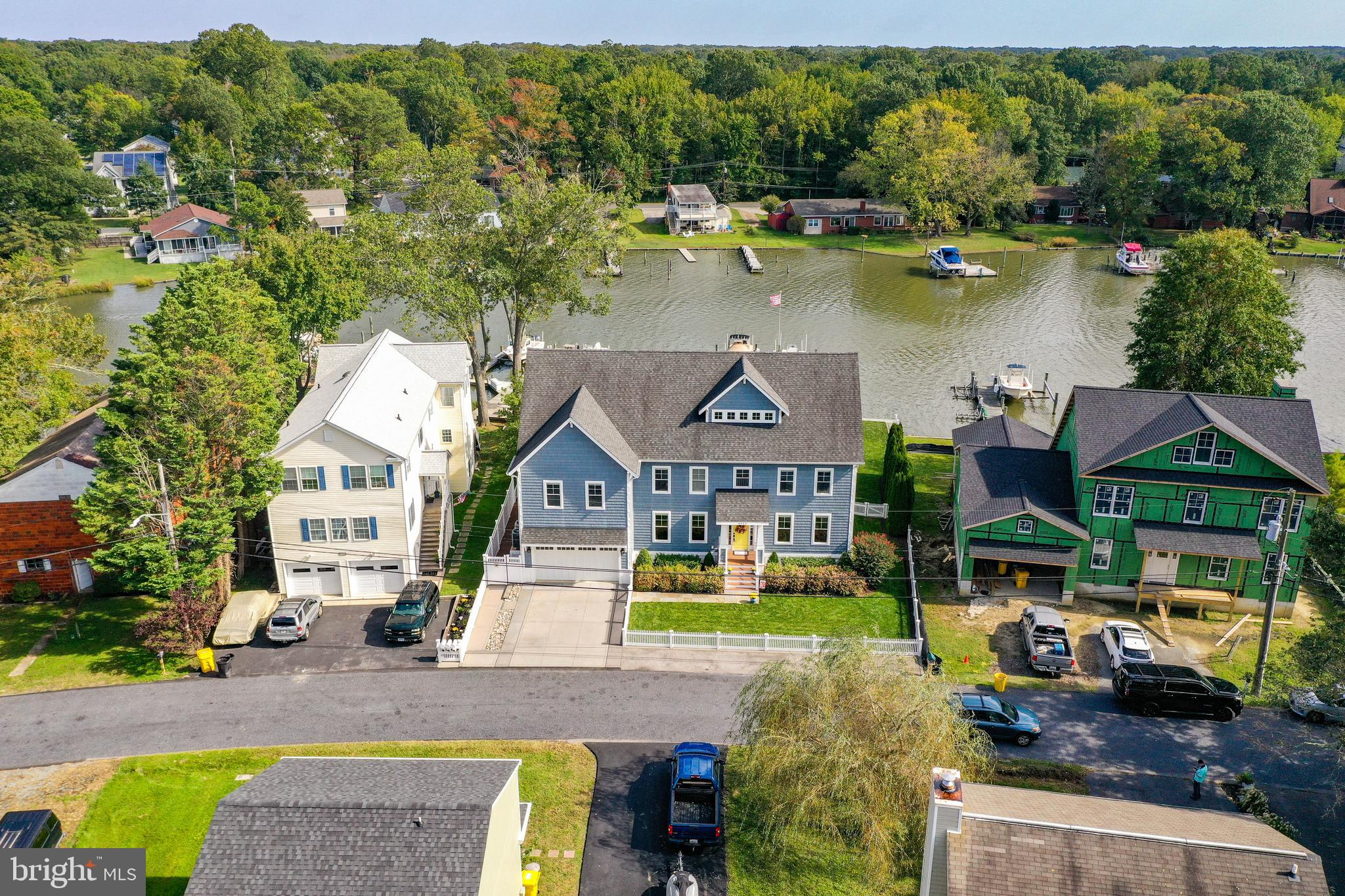 Stunning custom-built waterfront home!  Pride of ownership is easily seen in the upgraded materials and finishes that have been selected for this home, both inside and out. 4 bedrooms, 4 and half bathrooms!  It's a vacation everyday in this amply spaced home with three levels of living and recreation!  Spacious and open with tall ceilings on every level, 5 inch maple hardwoods, upper level laundry room, granite counters, SS appliances, double ovens, gas cooktop, storage closets aplenty throughout the home -and a separate exterior entrance on the waterside with tile floors and a full bathroom ...perfect for cleaning up after a long day out on the water.  Work from home with ease in the large home office located on the main level.  Owner's Suite boasts a grand bedroom en suite complete with walk-in closets, soaking tub, dual vanity sinks, a sitting area, bonus room currently being used as a workout space -and a private balcony to enjoy the peaceful water views in the early mornings or evenings.  Two additional bedrooms, a laundry room, a full bath, and a den/LR area are also found on the second level.  Better than a basement, the third level is fully equipped with a fourth bedroom, another full bath, extra large family room overlooking the water --with yet another balcony!  Wet bar and refrigerator...this space is an entertainers dream!  Windows galore!  Sunlight and outside views are your everyday decor.   Outside, the property sits along 100+ feet of water frontage with a spacious plush green lawn.  Additional exterior features include a white vinyl picket fence, an irrigation system, custom decked pathways, new bulkhead & pier with water, electric, two boat lifts, and a sun deck for relaxing and enjoying those perfect summer evenings -or welcoming home your favorite crabbers from their Bay adventure ...and so much more!!  Average water depth is 3.5 ft. Community amenities include a boat ramp, marina and swimming beach.   Close proximity to area parks, several local
