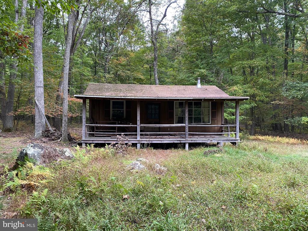 Ready to Be Finished -  Sitting on 5+ acres with well, septic, electric this cabin needs some TLC and your finishing touch.   One bedroom, bath and great room with wood stove.  Enjoy this private setting on the front porch.