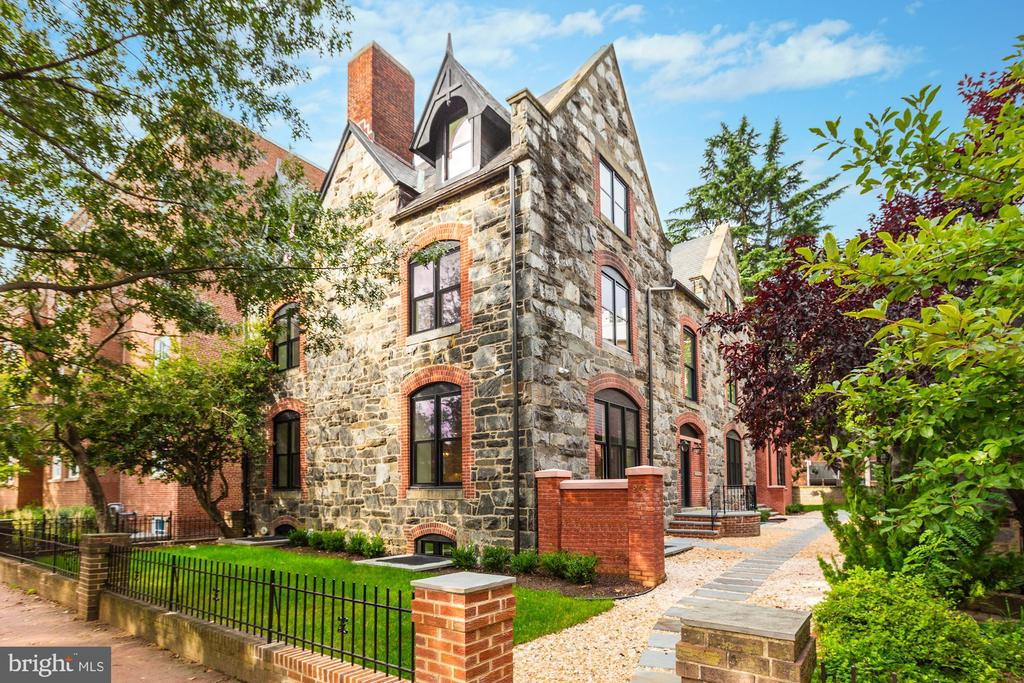 A timeless stone and red-brick facade shaded by mature landscaping captures the very essence of its charming setting, Historic Capitol Hill. Dating back to the late nineteenth century, Downing House was initially purposed as a church rectory for neighboring St. Monica and St. James Episcopal Church. The old church rectory has been completely reimagined to host two spacious luxury residences with every modern treatment and amenity. Spanning 3,900 square feet, Residence A offers 4 floors with 4-bedroom suites, 4 full bathrooms, and 1 powder room. The open chefs kitchen features a marble-clad island with a farmhouse sink, hand-milled cabinetry, Wolf & Bosch pro-series appliances, and fine glazed coffered ceilings, which add handsome architectural nuance to the main living spaces. Refinement is evident from every angle. From flickering gas lanterns to lacquered doors and banisters, hefty hardware and plumbing fixtures, flawless tile and masonry work, and rich solid oak hardwood flooring. The subtle handiwork of countless artisans is on display. Downing House is guaranteed to exceed the market standard. Plentiful custom paneling and soaring ceilings assure the feeling of grand-scale city living. Top-of-the-line audio/visual components were diligently installed throughout. Each bedroom is paired carefully with an en-suite bathroom and custom-milled closets. Spanning the entire second floor, residents are welcomed to the inspiring master suite boasting a massive walk-in master closet and a bath drenched in marble with a gas fireplace adjacent to a freestanding soaking tub. Garage parking completes the picture at Unit 1 at Downing House. Constructed with integrity by Berkeley.