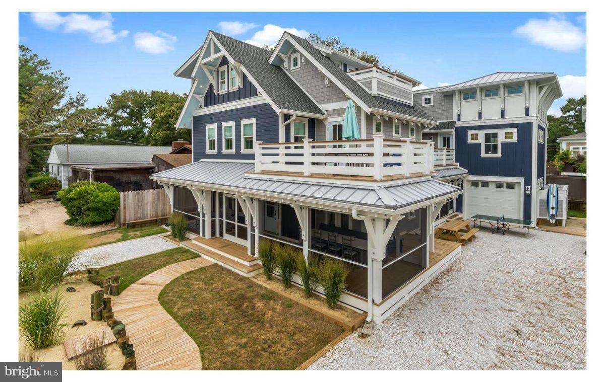 A fantastic custom beach home built in 2017 and located 1.5 blocks from the ocean in the Rehoboth-by-the Sea-Neighborhood between Rehoboth & Dewey Beaches.  In coastal shades of navy blue, gray and white, the exterior has been painstakingly trimmed, accented and designed with architectural elements, multiple decks, breezy screened porches, four outdoor showers, boardwalks and sand dunes.  Inside you'll find a California beach vibe with vaulted & cathedral ceilings, natural material trims and accents, gorgeous tile and amazingly durable white oak floors throughout.  Come take a look!    Features 7 bedrooms with a 3rd floor penthouse suite that can be considered an 8th bedroom.  A total of 7 full bathrooms each with whimsical tiled floors & showers, along with 2 half baths designed with fabulous vintage surf style.  The kitchen stuns in shades of blue and white, with natural wood accents.   Features a 6-burner Thermador gas range, Advantium oven/microwave, floating wood shelves and a statement backsplash of imported Moroccan concrete tile.  A separate beverage area enhances the flow and entertainment options with a copper sink, vintage refrigerator, 2nd dishwasher and banquet seating. The kitchen island of recycled glass is centered to a wall of sliding windows that open to the side porch and yard for indoor/outdoor entertaining.  Great room has built-in surround seating, and the cozy den provides a relaxing escape.  Relax on the 3 exterior decks and/or 3 screened porches.    Currently the garage is used as bike & beach storage, and has access to a full unfinished basement. An additional bonus room above the garage is currently used as a 14'x19' workshop / studio / storage area / look-out tower / 9th bedroom.    There is also a rear kitchenette / TV and game room with its own screened porch. This unique design has optional purposes to utilize the the entire home for large groups, or lock-off the rear section to create semi-private spaces or an in-law suite.  Come see it this weekend!