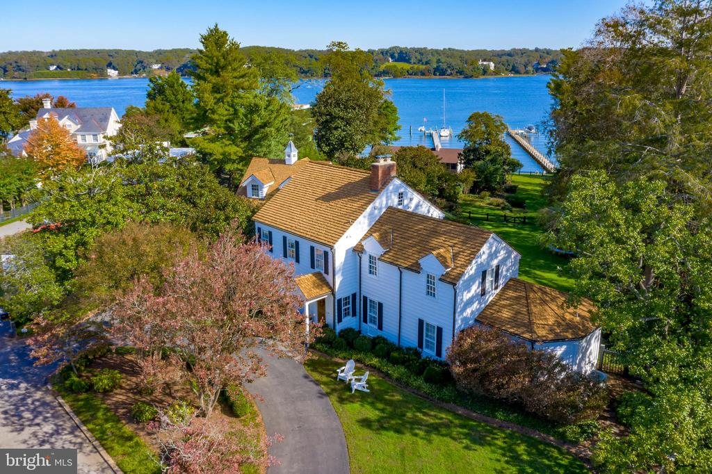 This prominent Annapolis waterfront home, built in 1948 by shipbuilder John Trumpy, sits on over an acre along the Severn River in the community of Wardour. Enjoy the ultimate entertaining space with waterside pool, outdoor kitchen and dining, large deck, and full pool bath. Embraced by boxwoods, crape myrtles, hydrangeas and gently sloping lawn to the water, 85 feet of water frontage, private pier with 3 deep water slips, boat storage cabana, and quaint potting shed. Beautifully updated while maintaining a comfortable, intimate feel and coastal waterfront styling, the main house boasts water views from almost every room. Offering 5 bedrooms and 6.5 baths  including a redesigned owner's suite. Enjoy the high end chef's kitchen with fireplace and adjacent family  room, formal dining and living rooms, plus library with built-ins. The walkout lower level includes a 2nd family room, wine storage and sauna. The Amish built two-car garage has a spacious private studio above with 2 open lofts, full bath and balcony overlooking the pool and water view to the Severn.