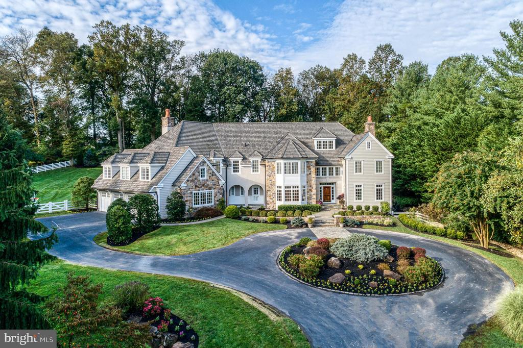 Experience the beauty, the move-in ready ease, and features that everyone wants of this exquisitely remodeled French Country estate in prime Berwyn on sought-after Grubbs Mill Road.  This exclusive, gated, custom residence sits on 2.3 pristinely manicured acres, with five bedrooms, five full and three half bathrooms, a 2015 swimming pool with spa and gas firepit, a 2,400 bottle temperature and humidity controlled wine cellar and tasting room with farmhouse beams and wine barrel flooring, and an expansive wet bar and family room for entertaining.  Upon arrival, this stately home affords a circular driveway with gracious curb appeal, surrounded by mature trees and lush landscape.  Inside, a grand foyer welcomes you home to a lovingly maintained retreat, complete with freshly painted walls, a light and airy floorplan, and several unique surprises too, including a reimagined master bedroom with massive walk-in closet, built ins, and generous spa bath.  At the heart is a fully equipped chef's kitchen with ample custom cabinetry, top-of-the-line stainless steel appliances, two dishwashers, and a center marble island that opens to a large breakfast nook and light-filled living room anchored by towering floor to ceiling wood paneled fireplace and walls of windows bringing the outdoors in.  Not one, but two oversized home offices are great for those who work remotely, complete with built-ins, added storage, and views, as well as one with separate entrance.  Bonus upper level loft is great for kid's homework with built-in desks.  Gorgeous designer details can be found throughout including Brazilian cherry hardwoods, stone flooring, custom wallcoverings, remote control shades, three gas fireplaces, a professional home gym with steam sauna, shower and separate dry sauna, plus sophisticated touches that make a house a home.  Outside, it's all about connecting with nature amidst a canopy of trees.  Here, a sparkling pool with spa and gas firepit and huge patio with a built-in gas grill add ambiance to family events, entertaining guests, alfresco dining, or simply well-needed time spent outdoors.  Additionally, off of the finished lower level, there is a natural firepit and koi pond with peaceful waterfall for unwinding.  Other highlights include a brand-new heating and cooling system, walk up attic with cedar closet, four-car heated garage, whole house generator, Pentair Easy Touch System to control the pool and all features, built-in Sonos Sound system with speakers inside and outside and fully fenced lawn with irrigation.  Living here puts you minutes from the best of Berwyn in a prestigious Eastown location, with exemplary schools, and quick access to the esteemed Radnor Hunt Club.  With the ultimate in privacy and 9,693 square feet of elegant spaces to live, work, and entertain, few offerings compare!
