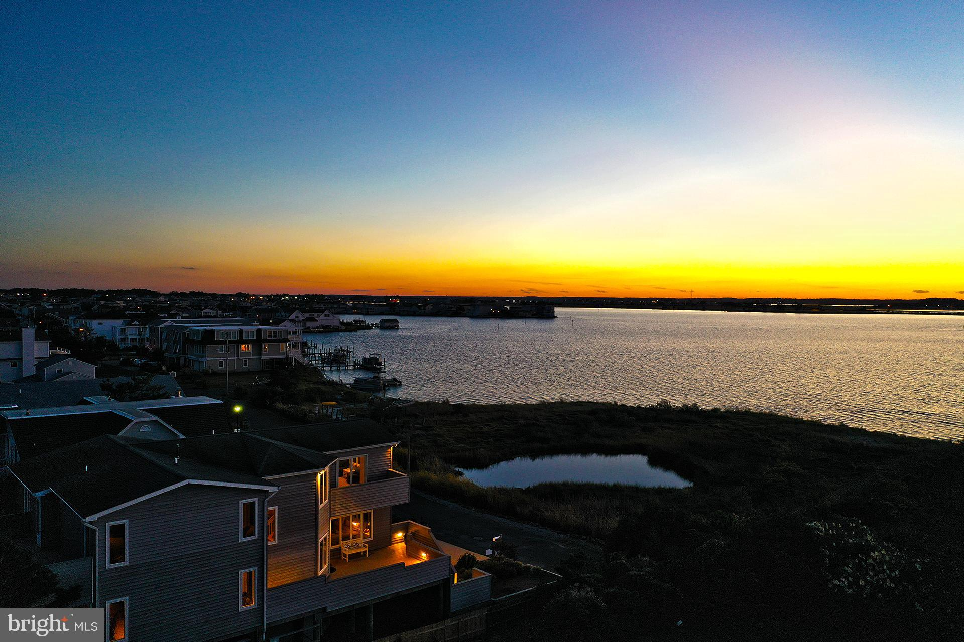 Welcome to the BEST panoramic views of the Little Assawoman Bay, located at the Northern tip of the Town of Fenwick Island, Delaware. This spectacular, Coastal Style, Custom-Built home offers 5 spacious bedrooms and spectacular views from every level as well as access to the Bay.  This home sits on approximately half an acre with property lines extending into the Bay.  This home includes 3 master suites with walk-in closets, 2 additional bedrooms, a spacious kitchen with a large island and walk-in pantry which leads to a screened in porch for enjoying outdoor eating.  The dining and living areas  take advantage of amazing sunsets over the Little Assawoman Bay.  The living room features a gas fireplace and built-ins that are enhanced with backlighting that make enjoying the incredible sunsets that much more relaxing.  Sunsets are also viewed from the owners' suite, owners' suite balcony and the living room deck area.  The home's outdoor features include beautiful landscaping, ample parking  for 8 cars (4 in the driveway, 4 under the home), kayak storage, patio area, 2 outside showers, and 2 secured storage rooms.  3 decks and 1 balcony provide ample outside entertaining and views of Fenwick Island and the Little Assawoman Bay.  The home has a water softener and filtration system, 2 gas hot water heaters, as well as 2 zoned heating and air conditioning.  The bottom HVAC unit is a heat pump with propane backup for those cold nights when you need more efficiency.  This delightful home sits on the Northern most waterfront lot in the Town of Fenwick Island and is a little over half an acre in size.  Don't let this opportunity pass you by.  Call to setup your tour today!