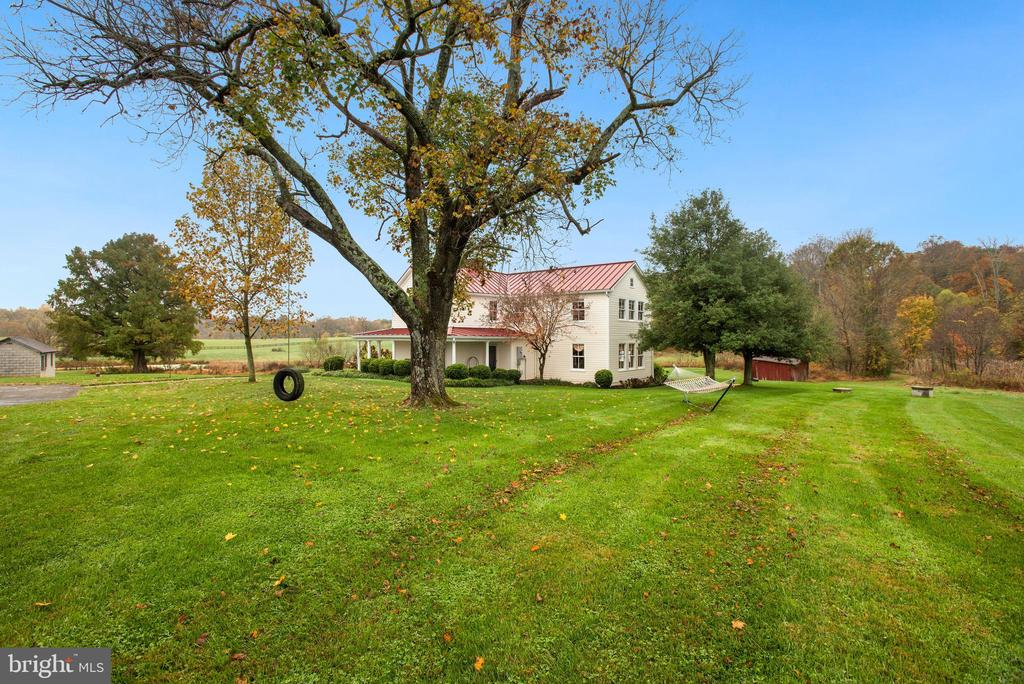 This stunning fully renovated 18th century historic estate is nestled on a spectacular 20 acres with picturesque 360 degree views and unrivaled privacy. Pride of ownership is evident at every turn, as homeowners have lovingly renovated this 1700's hand-hewn log home to maintain the historic beauty and charm, while providing 21st century conveniences. During renovation, great care, time and cost was taken to ensure the original log structure of the home was architecturally reinforced.  Enjoy relaxing on the custom outdoor flagstone patio overlooking the amazing pastural views, 8 acre stocked pond and endless trees and greenery. What a serene and calming site.  When you first pull into this magnificent estate, you are greeted by the Historic German Bank Barn built using posts and beams. New metal roof installed on barn in 2015. In great condition and awaiting your vision transformation: Winery, horses, home conversion- possibilities are endless!  The beautiful and inviting wrap-around front porch is just the start of the amazing experience when visiting 13330 Johnson Farm Lane. Upon entrance into the home, you will find an abundance of features and details that cannot be found anywhere else. This home is truly one of a kind. Original structure of home remains, while new additions were added over the years. The original heart of pine flooring is found throughout much of the home, while newer parts of the home feature aged ¾? solid oak flooring made from recycled fence boards. Much thought went into ensuring the new features tied seamlessly into the original historic features of the home. The kitchen is a dream, complete with custom designed cabinetry with restored built in cabinetry, stainless steel Kitchen Aid stove and dishwasher, center island and sunlit eat-in space. Adjacent to kitchen you will enter into the spectacular family room where you will be engulfed with the sense of historic feel- the exposed log walls and original stone fireplace remains, restored to i