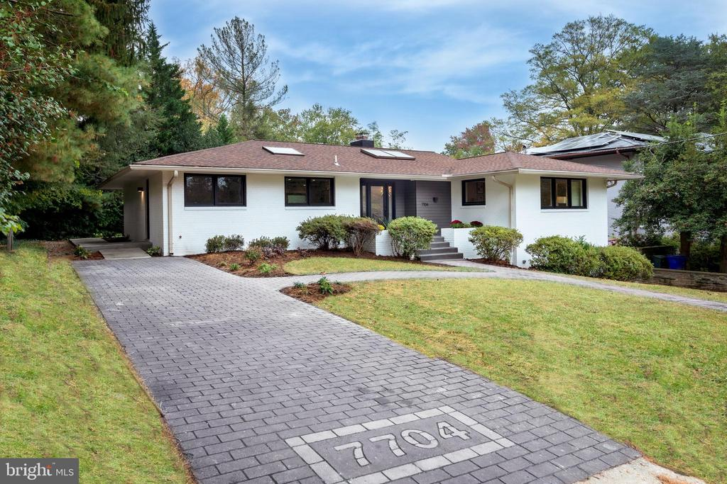 A fantastic opportunity to own a spectacularly renovated Mid-Century Modern home in Rollingwood.  The home was completely upgraded to current code and efficiency standards including insulation, windows, electrical and HVAC and redesigned slightly to provide a bright, spacious and luxurious living space while maintaining the functionality requirements of today's modern family.    This Contemporary Brick Rambler, with five generously-sized bedrooms and four full baths, is located in the Rollingwood Terrace subdivision of Chevy Chase.  The home is a comfortable oasis of tranquility situated on a private lot on a quiet street.  A walkway from the street and driveway welcomes you to a front porch and entry foyer with skylight. Immediately you are drawn into a dramatic, open floorplan kitchen and living/dining room with hard wood floors and recessed lighting throughout.  The bright kitchen, illuminated by yet another skylight has a spacious island with oak butcher block and Honed Avalon marble countertops, high end appliances, gas cooktop below a recessed, ceiling-mounted range hood, super-quiet dishwasher, built-in wine center and beautiful custom-made walnut kitchen cabinetry. The kitchen adjoins a combination dining area/living room with a stylish flat stone wall with fireplace and sliding glass doors leading to an intimate flagstone patio in the back yard. Both the living room and dining area are adorned with trayed ceilings and dimmable LED cove lighting to provide a warm, ambient glow to the living spaces.    The Owner's Suite includes an ample-sized bedroom with bedside adjustable reading lights, recessed lighting, and a huge walk in closet.  The Owner's Suite is capped off with a beautiful bathroom includes a European-style deep soaking tub surrounded by floor to ceiling tile and is adjacent to a curbless shower with linear floor drain and Polished Nickel Toto shower controls and handshower.  Dual vanities, adorned with marble tops and pendant lighting finish off 