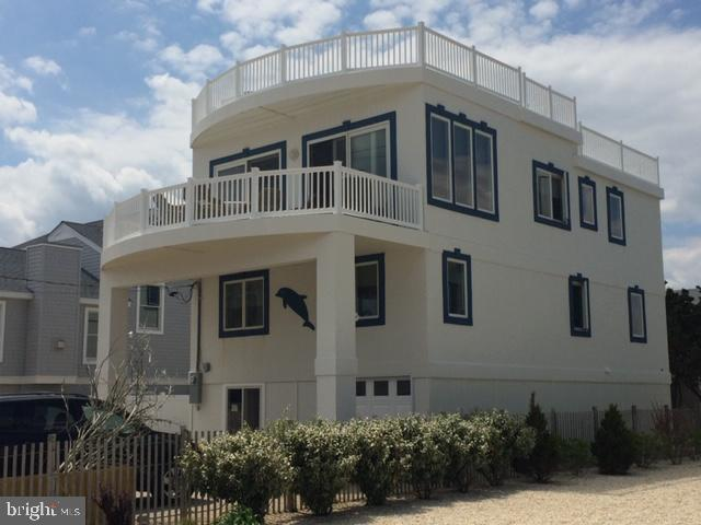 """Beautiful contemporary, aka  """"the dolphin house"""", sits on an oversized 50X115 lot, enough room for a pool.  This 5 bedroom, 3 1/2 bath reverse living home is well maintained and tastefully decorated.  The home features an open floor plan, perfect for family and friends.  Located directly across from the beautiful beaches of Holgate, views of both the ocean and bay can be enjoyed from the expansive rooftop deck.  A second deck, off the living room, is perfect for gatherings and barbecues.  Living room features a gas fireplace for those cooler fall days.   A functional kithcen includes newer stainless steel appliances.  Spacious dining area is perfect for large groups and the entire living area is flooded with natural light from the 2 sliding glass doors.  The entire home features hard wood floors except the bathrooms. This is truly a must see, you won't be disappointed. Interior photos will be provided soon."""