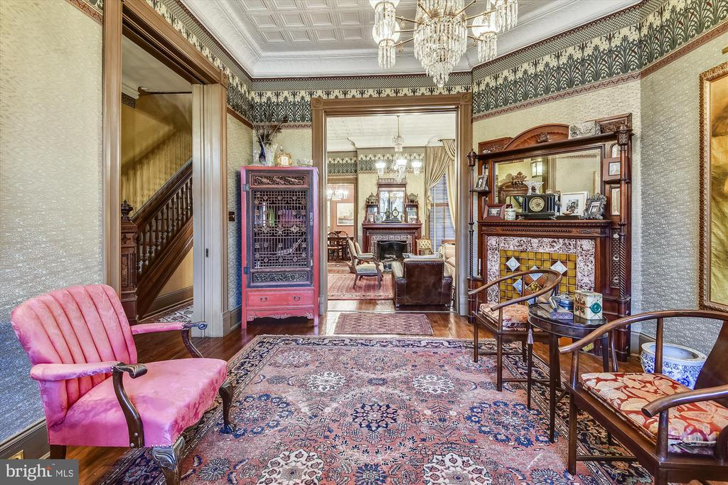 This classic and elegant Queen Anne-style, bayfront brick house was built in 1890, with many original features and details still exquisitely preserved today with a modern touch.   Original details abound from its carved, cherry and oak staircase,  pocket doors, the high tin covered ceilings to the richly covered  English William Morris  walls of the salon, living room and formal dining room with fireplaces and dry bar.   All embraced by three sparkling & stunning chandeliers and the original cast iron radiators providing comforting warmth.    The finishing touch on the Main Floor is the home's French country kitchen with commercial grade appliances and granite central island providing  Ample space for cocktails, preparing a feast or casual dining.  Kitchen features include a prep sink, seating, ample cabinets and a pantry for storage and wine racks.   Additionally a back staircase for late night snacking.   This all sits adjacent to a summer porch leading to a seclusive patio and garden.    As the two staircases lead you to the second floor you will find your main bedroom with fireplace and    continued elegance in two additional bedroomw with  high tin ceilings and classic wall coverings.  The final touch is the second floor is the spacious living area/study or even 4th Bedroom with carved wood mantel, built ins and original woodwork.  All this and also offering a full view of the US Capitol Dome from its bay window!   Finally this one-of-a-kind home, offers a fully functioning lower floor guest suite with street and patio accessibility.  A recent quality addition to the home it offers separate entertaining and sleeping quarters, a kitchen line, bathroom, den/bonus room in the rear, and two fireplaces.   Convenient to Brent School, METRO, parks & playground, this premier Capitol Hill home lies a stone?s throw to US Capitol, and the restaurants, shops and entertainment of Eastern Market, Barracks Row and Pennsylvania Avenue.  Truely, this extraordinary home defines 
