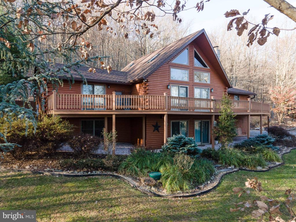 Beautiful Custom Built Log Home -  Professional landscaping, a waterfall, patios and lots of natural rock boarders.   2.51 acres with panoramic views.   This home features:  3 Bedrooms, Game Room or 4th Bedroom, Great Room with stone hearth & woodstove, skylights, wall of windows, doors onto front deck and a open Loft.  Gourmet Kitchen w/granite countertops, center island, and Dining area.   Formal entry foyer, 3 Baths, Family Room with stone hearth and woodstove plus lots of windows to let the natural light in.   Laundry Room, two car garage, PLUS so much more!  This property also backs up to Cacapon State Park.