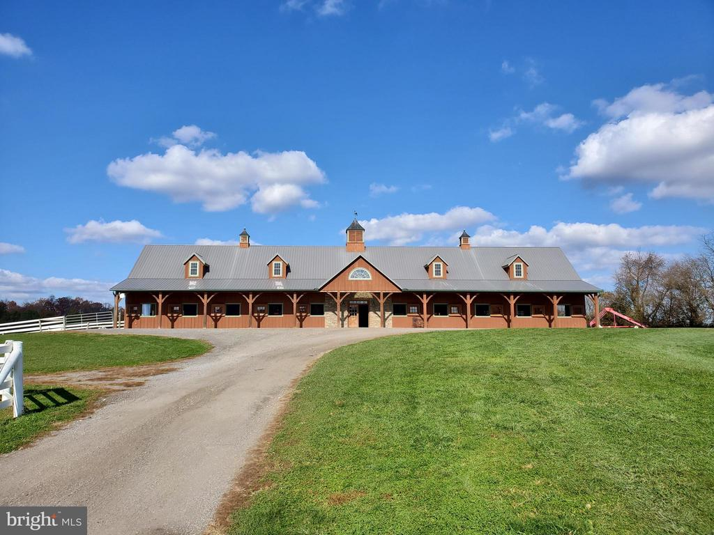 *** This is the Equestrian Training Center of Your Dreams! *** Look No Further!  Do you dream of training horses, teaching lessons, offering top caliber sales horses, or incomparable boarding services in the heart of Howard County?  Do you want a custom built barn with a state of the art indoor and custom footing?  Ready to take your competition horses to the next level with space for a large cross country course and full outdoor jump ring?  This farm is an incredibly successful boarding business for good reason.  Every element of this facility has been carefully curated to offer you, your horses and your clients the utmost in care, comfort, and amenities.  This farm offers 60 acres, 26 stalls, indoor and outdoor arenas, and an adorable updated farmhouse along with second homesite ready for your architect's designs.  The Main Barn set atop the hill offers thirteen stalls, a large nonslip aisle way with cathedral ceilings, thirteen matted stalls with removable yoke stall fronts, a tack room with custom lockers, and a climate controlled viewing lounge.  The viewing lounge is the perfect respite for your clients to review training videos, plan their competition year, or connect with each other over coffee.  The lounge offers a full viewing gallery with direct views of the state of the art indoor, a half bath, custom wet bar with full refrigerator, and a laundry closet.  Imagine hosting international clinicians here and inviting your guests to a catered lunch.  This spaces will make everyone feel welcomed and at home.  The indoor features sliding windows and four large doorways flooding the space with ventilation and daylight which makes it both reassuring and safe for your top horses.  The footing is a blend of stonedust and sand and the LED lights mean riding after dark is possible with minimal shadows.    For those clients wanting a more boutique setting, there is a seven stall barn at Cedar Lane as well.  This barn also offers a center aisle construction with nonsli