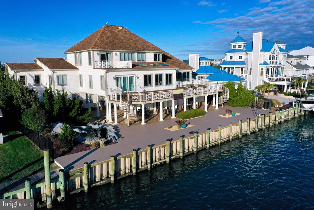 Rare Opportunity to Own one of the Finest Bay and Ocean Views Homes available in West Ocean City. This Spectacular 6 Bedroom, 6300 Square Foot Coastal Waterfront Masterpiece  is Situated on a Deep Water Bulkhead within eyesight  of the Atlantic Ocean and Inlet and Will Accommodate Deepwater Dockage for up to an 80' Sport Fishing  Yacht. Grand Open Vistas of the  Bay, Ocean and Assategue are Truly Stunning and Available from All 3 Levels of this Magnificent Coastal Home.  This Wonderful Home Boosts  a 4 Car Garage and an Elevator to Service All 3 Levels.  The Second Floor is the Main Living Area Offering Commanding Waterfront Views of the Bay, Ocean, Assateague and Commercial Harbor, The Spacious Kitchen has  New Stainless Steel Appliances, Butlers Pantry, Abundant Cabinets, Granite Counter Tops, Island and Eat-in Area facing the Open Bay and is a Great Gathering area that Leads out to the Southern Exposed Waterfront Decks,  There is also a Formal Dinning Room, Great Room with Vaulted Ceilings, Billiard & Game Room and Super Bay Front Master Suite & Bath as well. Third Floor has another Master Suite With Southern Coastal Views  from the  rear Large Deck.  Additionally, there are 2 more Bedrooms on the 3rd Floor that are serviced by a Jack & Jill Bath. This First Floor has 2 More Bedrooms, a second Kitchen and Living Area and access to Multiple Garages and Rear Covered Waterfront Patio, This Waterfront Home has many unique Features including 2 Huge Laundry Rooms on separate levels, Plenty of Storage Closets, Workshop, 3 Natural Gas Furnaces and One Heat Pump, Gated Driveway for the Ultimate Privacy & Security,  There is also a Sound Speaker System throughout Home, Fencing on 3 Sides of the Property with Mature Landscaping and Situated on a Double Lot offering 100 Feet on the Water. A New Vinyl Bulkhead recently  installed and New Ground level  Vinyl Deck. This Property is Directly Located Across from Sunset Marina the Play Ground for the World Sports Fishing Anglers! The Large Covered Patio is an Amazing Place to Hangout,  Watch the Boats Go By, Entertain and View the Sunsets. This One of Kind Property  has to be  Seen to be Truly Appreciated.  Come Down to the Land of Pleasant Living and Enjoy Coastal Living at its Finest. Check out the Virtual Tour.