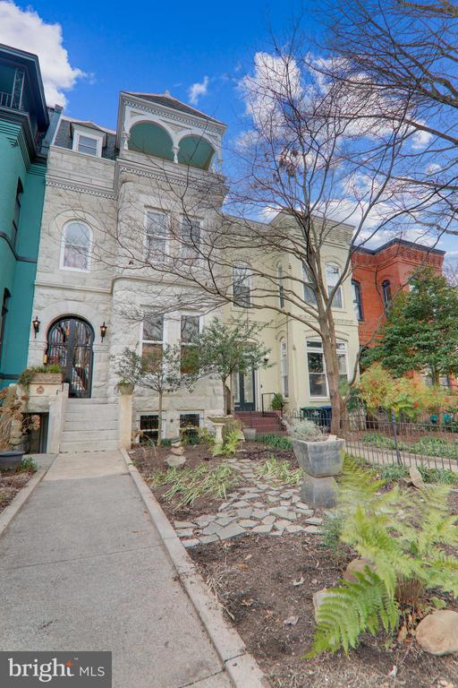 THE GRANDEUR OF EAST CAPITOL with stunning chiseled alabaster marble and iron gated exterior of this 4BR/3.5BA home is just the beginning and add a lower  level 1BR unit ($2600+/MO).  Inside this home built in 1875, you will find custom architectural detail blending old and new, soaring cathedral ceilings, two primary bedrooms with en-suite baths, third floor balcony, income producing solar panels, and much more.  As you enter the home, the grand living room and formal dining room are both in your panoramic view. Separated by trimmed cut out walls and archways, the main level space is excellent for entertaining without giving way to the modern open concept. History is preserved with three stunning fireplaces on this level. The grand proportions of the eat-in kitchen provides brilliant sunlight with a south facing two story glass archway.   Moving upstairs to the second level is an open balcony overlooking the kitchen below. A hallway with plenty of storage leads to the first of two primary bedrooms, featuring a dressing room with custom cedar walk-in closets, connecting to the full stone and glass bathroom where you will find even more custom features. The third level provides a second primary suite with walkout balcony overlooking all of East Capitol Street. Two additional bedrooms and one bathroom also adorn the top level of this home.  The lower level of the home contains a separate 1BR/1BA English basement apartment (with C of O) that can serve as a guest suite or be used for rental income.  A stone's throw from lovely Lincoln Park, and walkable to fine dining, daily errands, METRO/Amtrak, Eastern Market, Barrack's Row, Union Market, this home is in one of the most sought-after Capitol Hill neighborhoods and is truly a must-see.