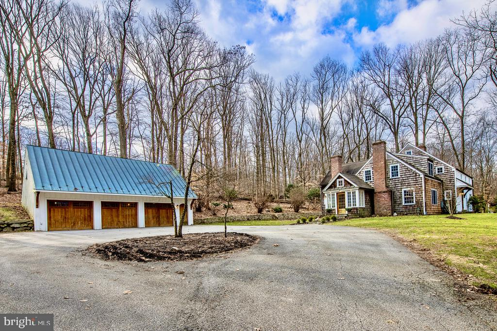 Welcome to 536 Clothier Springs Road. Perfectly situated on a beautiful 2+ acre property on top of Valley forge mountain in the Great Valley school district this unassuming New England farmhouse style home blends in perfectly with its natural setting. The house is accompanied by a custom built detached three stall garage with a huge unfinished walk up loft space and its own electric panel. From the garage or driveway you will enter the house using the side entrance which leads into a perfect  entry way mud room with brick flooring warmed by radiant heat and custom built in closets and moldings. The lofted ceiling and ample windows make this a very bright and welcoming space. The family room is next and its a beauty! With a large fireplace as the focal point, built in speakers and surround sound, radiant heated wide plank flooring and custom built in cabinetry everywhere this might be the perfect family room. The family room leads into the kitchen area and to the huge dining room which also has a fireplace, radiant heated floors and more custom built in cabinetry. The eat in kitchen has lots of counter space including an island with smaller prep sink. The solid wood cabinets along with a large  pantry closet offer an abundance of food and kitchen item storage.  The kitchen is centrally located on the first floor and has direct access to the  large covered and open air rear patio. On the far side of the kitchen is the office area which can be closed off and also has access to the rear patio. The other side of the office leads into the formal living room which is located in the front of the house and features another fireplace and more built in shelving and cabinets. The living room leads to the front foyer and entrance hallway where the front door of the house is located. The foyer is where the first floor bathroom and stairway to the second floor is located. The second floor has all four bedrooms and three full bathrooms and well as multiple storage closets and a hallway laundry room with a stackable washer and dryer, sink and counter top. The hall bathroom is nicely sized and has a frameless glass shower/ tub combo. The second full bathroom in located in one of the bedrooms and has a newer vanity and updated stall shower. This bedroom much like the rest of the house has amazing closet space for clothes and storage. The highlight of the second floor is undoubtably the master bedroom suite. The master bedroom is large and features custom built in drawers and storage as well as two walk in closets. The bedroom leads seamlessly into the gorgeous master bathroom which fits the esthetic of the home to perfection. The custom wood and marble vanities along side a large soaking tub and oversized stall shower and radiant heated wood floors give this bathroom a luxurious yet authentic feeling much like the rest of the house. While unassuming at first glance this home has more to offer than meets the eye. This is a special place to call home!