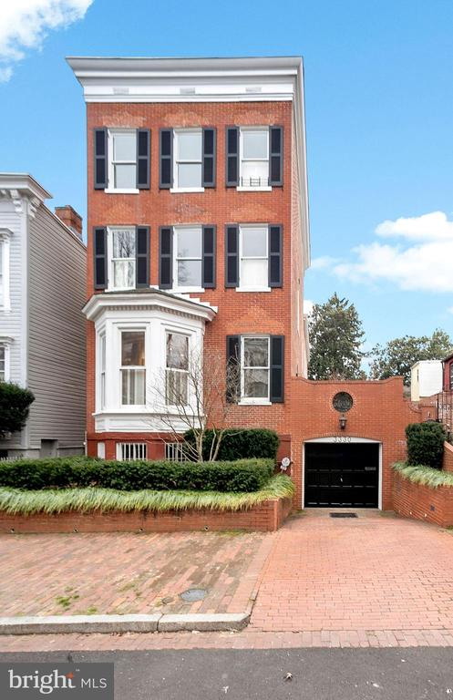 Simply magnificent, detached red brick Federal on one of Georgetown's most authentic and historic blocks. Once home to Robert Kennedy, this grand house has wonderful views of Cox's Row across the street and is the same block JFK left for the White House. The house has all the attributes one would expect from an important detached home; large windows for great light, ample gas fireplaces throughout, and large scale spaces with high ceilings and original details. The entry level enjoys light from four exposures and has the coveted floor plan of an eat-in kitchen, separate dining room, spacious living room and library all on the same  level. There are six bedrooms and four full baths with two half baths. The spaces in the house are both delightful and flexible, with extra bedrooms transitioning into excellent home offices, fitness rooms, or live-in spaces for help. There are terrific gardens on the side and the rear and a playhouse. There is two-car parking, including a one-car garage with a Tesla charger.