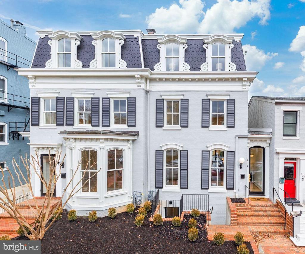 Created by Brush Arbor Home Construction's masterful collaboration of architects, interior designers, and landscape architects, this total renovation of one of Frederick Douglass' former residences is a four-level Second Empire-style elevator townhouse of impeccable elegance and exceptional scale. Providing bespoke tranquility in a coveted location just a couple blocks from the Supreme Court, Capitol and Senate Buildings, no detail has been overlooked in the custom renovation of this architectural gem.  Here, luxury and sophistication clearly meet modern day amenities and lifestyle needs.    A spectacular open floor plan integrates 10' ceilings, custom interior and exterior millwork, hand-milled white oak floors, Jeld Wen windows and doors, designer bespoke finishes such as lighting by Visual Comfort and fixtures by Kallista and Waterworks; all provide breadth and airiness on the main level. The front foyer's brick accent wall offsets the generous living room with fireplace and classic bay window, both complemented by the highest quality fixtures and finishes. There is a seamless flow from indoors to outdoors from a custom 15' wall of glass windows and doors to the private terrace, capturing an abundance of natural light adjacent to the chef's kitchen with its rigorously curated appliance package and breakfast room. The second level features a large landing and includes a well-appointed primary suite with two walk-in-closets, and spa-inspired bathroom. All five secondary bedrooms, spread across three levels with elevator access echo the primary's luxury finishes and closet or dressing room space.   The penthouse level offers a sublime north-facing city view from the relaxing vantage point of a family room with wet bar. The exceptionally crafted lower level includes an exercise room, second laundry room, as well as a secondary bedroom on this level. Access to the garden from the lower level thereby provides excellent flexibility for au-pair or in-law living configurations. The exterior has been planned with the utmost discernment, executed to provide a private backyard retreat which features a stone patio, shaded by strategically chosen, well-placed greenery, and a 2-car garage. The residence also conveys with two additional one-car garages across from the alley, just kitty-corner to the NW rear corner of the property.