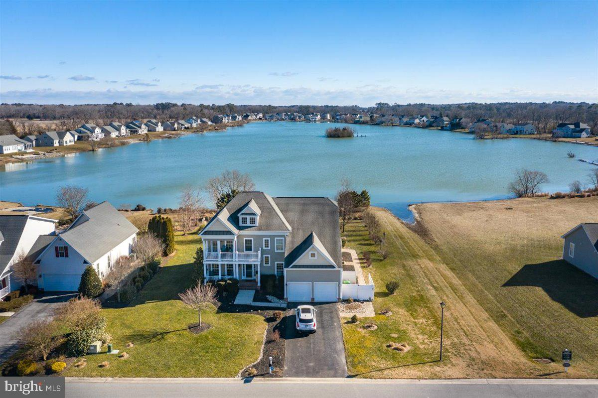You will find pure joy creating your next chapter in this home!  Expansive pond views  from almost every window in this spacious property in sought-after Hamlet at Dirickson Pond located less than 6 miles to Fenwick Island and Bethany Beach.   38 acre pond spring fed pond allowing non-motorized boating, catch and release fishing, community clubhouse and pool. Welcome your guests into your impressive home through the foyer with 2 story ceiling and a striking grand staircase.  To the left you will find a formal living room and dining room which is perfect for large gatherings.  The oversized gourmet kitchen features a desk area, large pantry, wall oven, cooktop with pop-up downdraft, large center island, breakfast bar, expansive granite counters, beverage center, and morning room.  There is endless possibilities for entertaining on the large rear screen porch, stamped concrete patio, and huge rear yard complete with your very own putting green.  Access to the pond from you own private beach is great for launching your kayak, canoe, and paddleboards!  The great room is flooded with natural light from the many windows across the back of the home where the views of the pond and wildlife is breathtaking.  Gleaming hardwood floors through most of the main level living areas, gas fireplace, and ample lighting create a wonderful space for everyday use.  You will also enjoy having your office/5th bedroom located off the great room as well as a powder room, and laundry room for ease.  On the second level you will find an owner's suite sure to impress with two walk-in closets, recessed sitting room, and bath with two separate vanities, water closet, soaking tub, and separate shower.  3 guest bedrooms and 2 full bathrooms provide ample space for overnight guests.  One bedroom has access to a private half covered balcony.  Again, the views from the back of the house is out of this world.  Enjoy the community clubhouse and pool.  Recessed Lighting in Every Room, 4' Crawl Space, HVAC replaced, Energy Efficient Appliance, 2 Car Garage, Irrigation System.