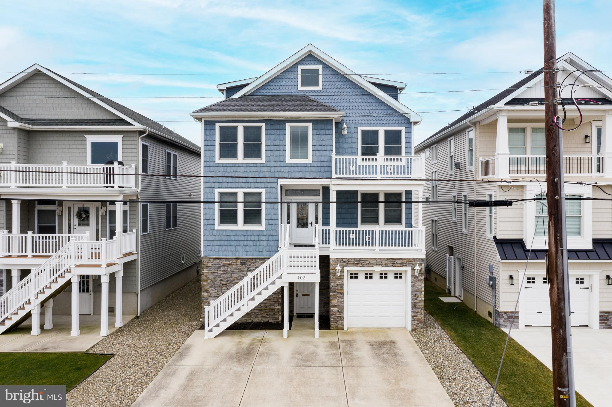 Now is the perfect time to take that next step you've been dreaming of. The time is perfect for you to purchase your shore home in the great town of Brigantine. This beauty offers views of the ocean and the bay and has more space than you can imagine. It is designed with the vacation fun and entertaining lifestyle in mind. You'll love the street presence with the blue maintenance free shingle, siding and stone facade, multiple levels of decks on the front and rear, off street parking in the cement driveway and a one car garage. There's even a grassy backyard for the family and pets to play. The raised design of the floor plan creates a street level space next to the garage that is great for storage or ready to be finished off into game & entertainment space if you choose. The home also has an elevator for convenience. Your main living areas have engineered hardwood t/o, loads of bright sunny windows, a Great Room, Dining Room area, gourmet Kitchen with sophisticated styling, 6burner gas cooktop w/ hood, icemaker, double wall ovens; manufactured hardwood t/o, recessed lighting and all the furnishings are included in the sale. Two Bedrooms a full bath & half bath are located on the main level while the upper level is home to 4 Bedrooms and 2 additional bathrooms. Your upper, attic level is also ready to be finished into even more living space and it's ready to go. You'll even find a supply of matching hardwood flooring is ready and waiting for you.  Home has walkability to the ocean and the bay restaurants, shopping and all the fun activities that the shore provides.  Now is a great time to take the leap, rates are cheap and this home is perfect!