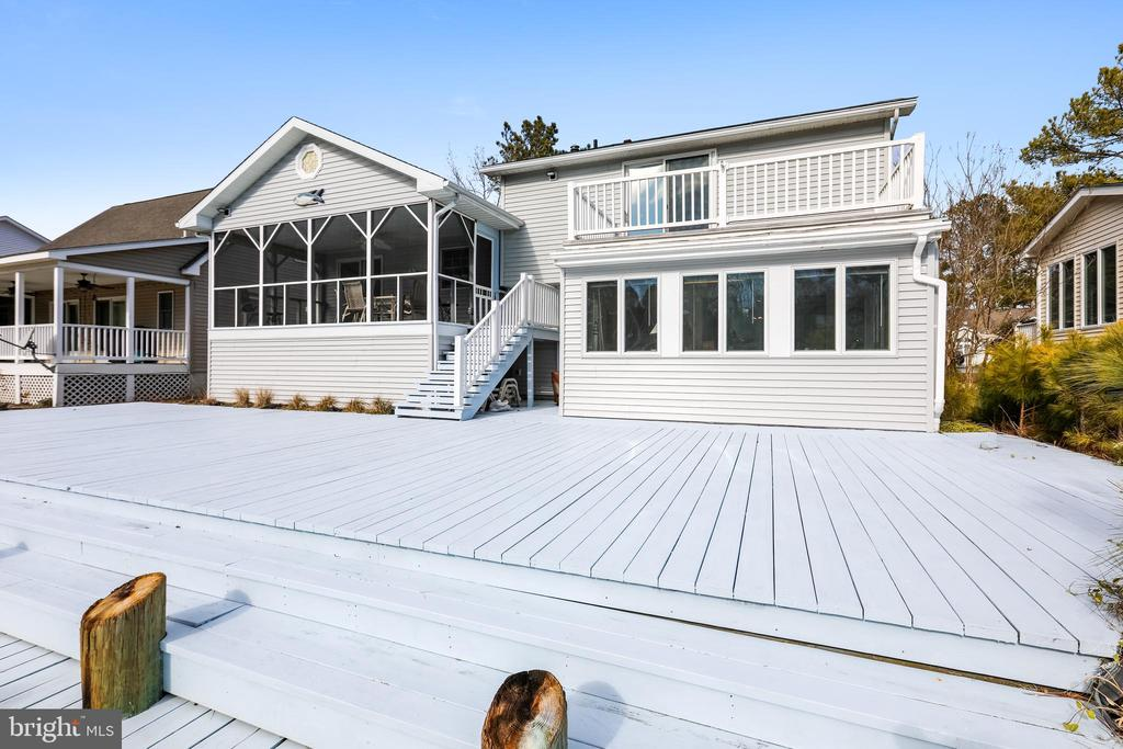 Luxurious living is guaranteed in this amazing waterfront home. It offers a perfect balance of style, functionality and space with ease of transition between indoor and outdoor living.  Since it is all about the water, you will love the 40 foot dock with electric boat lift up to 10,000 pound capacity. This home was configured for outdoor entertaining and includes a 50 foot freshly painted waterfront deck, a screened porch overlooking the water, a sunroom with the water view, a rooftop balcony with sliders from the master bedroom, a storage shed, upgraded LED outdoor lighting and a sunny front porch for rest and relaxation that was also just painted.  Space is plentiful inside this 1,888 square foot home with 3 bedrooms, 3 FULL bathrooms, living room, family room and country kitchen with new light fixture.  Special features include a whirlpool tub, cedar closet, pellet stove, hardwood floors, six ceiling fans and an attached garage with tons of storage.  Residents of this exclusive, amenity rich community called Ocean Pines enjoy indoor and outdoor swimming pools, a beach club in Ocean City, a Robert Trent Jones championship golf course, a new clubhouse, tennis courts, pickleball, a dog park, a yacht club with marina and much more.  This home is move in ready and priced to sell.  Schedule a tour today.  Furniture and furnishings are negotiable as  a purchase separate from the home sale.  The boat lift has a broken mount.