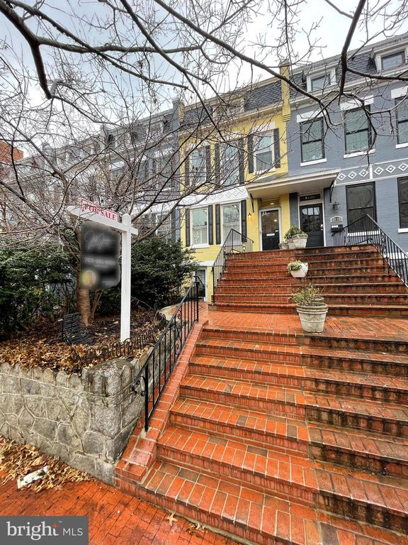 Welcome to your stately four-story Dupont rowhome that has been thoughtfully updated with two separate additions while retaining its historic finishes. As you enter, you'll notice gleaming hardwood floors in inviting living and dining rooms with a fireplace and custom built-ins. The chef's kitchen and recently added family living area flow into a covered and screened patio that is an ideal entertaining space. The second level features a master suite features with a walk-in closet and jetted soaking tub. Two other well-lit bedrooms share a bathroom with a jetted top.  A 2014 addition of ann incredible fourth level wows with a kitchenette, large open room, living/working space, and an additional bedroom. Then escape to a huge rooftop deck, irrigated rooftop garden, solar panels powering the house, with a great view of the 4th of July fireworks, the National Cathedral, and sunsets over DC.  Downstairs, the in-law suite with duel entrances includes two bedrooms, a full kitchen and remodeled bathroom, separate zone heating/cooling for each room, and an additional washer/dryer; with monthly rental/AirBnB income of approximately $4,000-$5,000. The house comes with covered parking for 2 cars and an electric charging station, built in surround sound on multiple levels, and extra built in storage sheds in the front and back add to the appeal. Ideally located with less than a 5 minute walk to Dupont Circle and the Dupont Metro Station, blocks from Foggy Bottom, Whole Foods + Safeway, countless restaurants, Georgetown, and downtown DC...schedule a tour today!