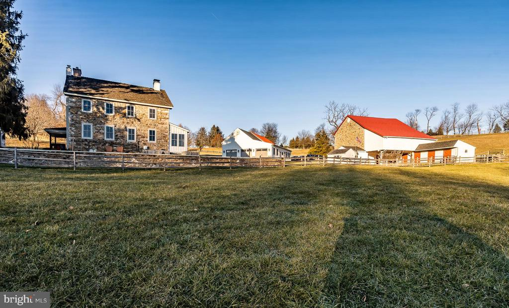 This beautiful farm is nestled in a hollow, with a light, bright, antique stone home, a historic barn, and 4 outbuildings, all set on 18 rolling acres. The date stone on the home states 1833 but the oldest part of the home has been researched to be c.1798. The fabulous stone bank barn's date stone states 1819 and was constructed by a veteran of the War of 1812! The current owners have done a magnificent job of staying true to the home's original historic heritage while also installing designer magazine worthy modifications including a new gourmet Kitchen complete with high end stainless Thermador appliances including a steam convection oven and a state-of-the-art coffee maker – both set in beautiful custom cabinetry that features two large pantry cabinets. You will love the Kitchen's easy care but period correct brick floor and stunning live-edge English walnut island countertop. The Living Room features random width wide-plank floors and the home's original cooking fireplace with its grand opening and original wrought iron crane. The windows include curved plaster work and deep windowsills making this a bright room with a priceless view. The other end of the Living Room displays a handsome corner fireplace with a super-efficient and beautiful wood burning insert. Off the Foyer is a handy Powder Room and the Kitchen access with the Laundry conveniently located off the Kitchen.  Walk outside through the Kitchen's French doors to find a large covered porch that is a perfect place to entertain friends and family. A second covered porch is on the west side of the home and is an ideal location for the grill and a quiet drink on a summer afternoon. Rounding out the rooms on the main level is the Office with a charming corner fireplace and a window with original period moldings. Upstairs is a wonderful Master Suite, with a sumptuous marble Master Bathroom, another added feature the owners installed and could also grace the pages of a designer magazine. There are three addi