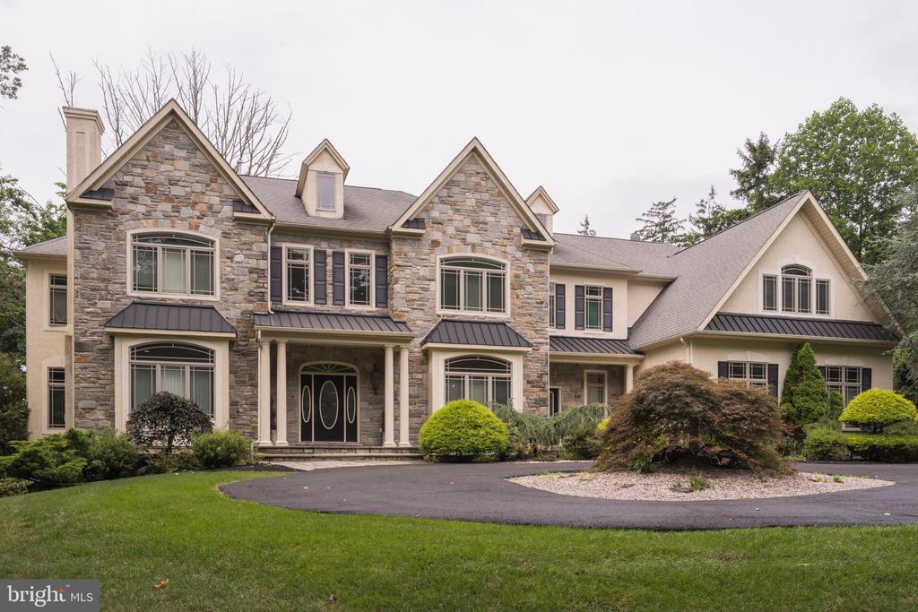 This five-bedroom, five-full bathroom & one-half bathroom contemporary mansion located 1514 Cherry Lane, Rydal, PA 19046 hosts an impressive exterior style that gives expansive interiors and luxurious features throughout its two stories of accessible, sprawling spaces.  As you make your way into the home, its persistent high ceilings, over-sized doors and arched doorways create a relaxed and airy atmosphere that achieves natural and unrestricted movements at every turn. One of the homes major focal points; the grand family room sets the tone for the rest of the home, with expressive high ceilings, a stone fireplace, a large window wall overlooking the private backyard and broad arched openings that allow a point of view to and from the gourmet Kitchen and bar area. Within the bar area; visitors will find that its granite counters, handcrafted wood cabinets and convenient bar essentials beckon a moment of your time and leisure. The upscale kitchen area features an eat-in setting and the freedom to cook effortlessly, with an over-sized two-level island and sink, sprawling cabinetry and multiple seating areas complementing the stove and countertops. A large pantry and a custom built-in refrigerator, wolf stove, pot filler, gas-cooking features, rising tile backsplash and finished granite countertops leave nothing to be desired as you prepare a meal or breeze through unnoticed for a snack; the second staircase offers immediate access to the second level from the kitchen. A nearby built-in desk with drawers and glass cabinets complete this area, from where you can pass through a glass door leading directly to a spacious deck spanning the rear of the home.  The outdoor deck made from picturesque wood spans two levels and can be entered from both floors of the home, where an ideal space for outdoor entertainment, cookouts and tranquil relaxation day and night is easily accessible and equally inviting. The backyard, lined by trees and colorful flowers and shrubbery, creates a private ambiance that extends from open green space to back deck and achieves a smooth transition from home to outdoors.  Back inside, the spacious dining room area accommodates your family and guests with classic high-grade wainscoting, a tray ceiling and palladium windows with a broad view outdoors. Into the Living Room, an exquisite crown molding and fireplace surrounded in tile and wood mantel express the comforts of home with a touch of luxury. Completing the main level are a large office with a tray ceiling and glass door leading to the rear deck, a full bath, a powder room, a mud room with tile flooring, a storage bench and a second exit to the front of the home.  The fully-finished lower level features a second family room and large wet bar, with exclusive tile flooring, a sink, handcrafted cabinets and a private seating area. The lower level expands into a media room, hair salon room with hair sink, a full Bath with tub, an additional bedroom, multiple storage areas and a bonus room where stairs lead to a set of doors that open into the four-car attached garage as well as the outside rear patio. Ascending to the homes second level from the main stairs, the steps lead to a Juliet Balcony overlooking the two-story family room below, with a double-door linen closet, an attic door, and hallways leading to multiple bedrooms connecting all areas of the second level. A tall double-door entrance leads to the stunning master bedroom, which features a tray ceiling, two walk-in closets, a large sitting room, a make-up area, a sliding door that opens to a private balcony, and the master bath with a tile floor, Jacuzzi, two sinks, a water closet, a vaulted ceiling, a linen closet, coat closet, and an over-sized shower stall with a bench and double shower heads offering amenity and splendor. Back into the hallway, the second level expands into three additional and spacious bedrooms, laundry room, and two full Baths.