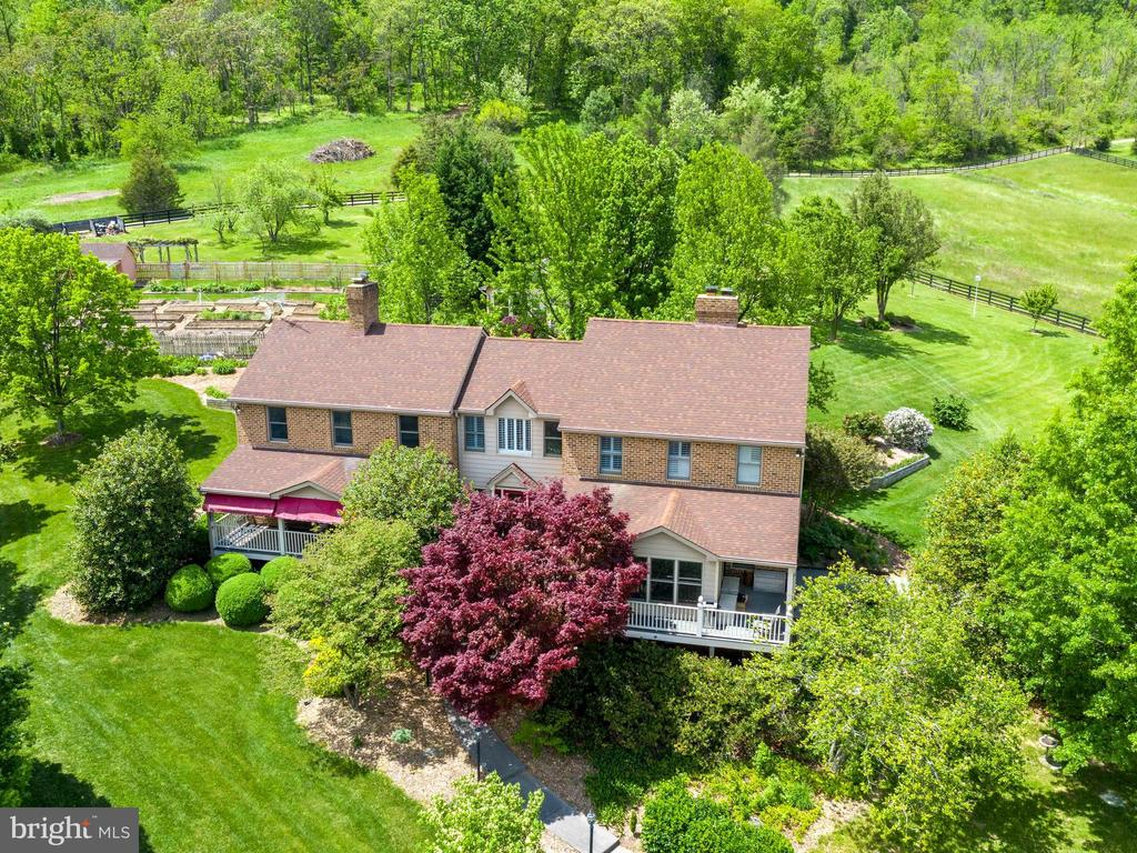 "Horse/hay farm in a serene park like setting 3.5 miles west of Winchester city limits . 21 acres of gently sloped, arable land with 5 bedrooms/3.5 bathrooms (see note below) with front and back porches; plus, front and back sun rooms. A special  feature  of the home are the beautifully patined  heart of pine floors on the main level and part of the 2nd. level. 6 large out buildings and 6 small outbuildings, large vegetable garden, 2 wells and 2 septic systems. Property designed for both entertaining and subsistence living. Horse stable contains 6 stalls, office tack room and 1/2 bath, heated wash room and 2nd. floor apartment with 1 bedroom/1 bath. 2 large/3 medium fenced fields and 2 paddocks. 8 water spigots in fields, garden and stable. Boundaries of the property are marked by the outermost black fences.  Located on the west side of Winchester (between Rte. 50 and Cedar Creek Grade) within 4 miles of Medical Center and on a quiet black top state road in tranquil setting of nice acreages.Enter via a curving driveway that passes the property""s stocked pond. Mature, well maintained landscape (beautiful trees, shrubs, irises peonies and day lilies); plus, 30 raised vegetable beds within a fenced area. A large pavilion features a fireplace, hot/cold sink and half bath; plus, an attached greenhouse/solarium (propane heat and hot/cold sink)Spacious 4 car detached garage with 2nd. floor overflow sleeping/full bath and entertainment area; older bank barn (new metal roof)/silo; heated building that has been used for art studio and  playhouse. Three run in sheds, two chicken coops and a garden shed. Other potential uses for this property are  personal vineyard,  raising up to 20 head of cattle and ?  All this is located on the east side of Little North Mountain with views to the east of hundreds of acres of agricultural land and over the Shenandoah Valley to the Blue Ridge Mountains and to the west of the Allegheny Mountains.. First named ridge of Allegheny Mountains (west of Winchester) is Little North Mountain which is the location of the property.  ***NOTE: The house has a  3 bedroom septic certificate which supports 6 adults living in the house."