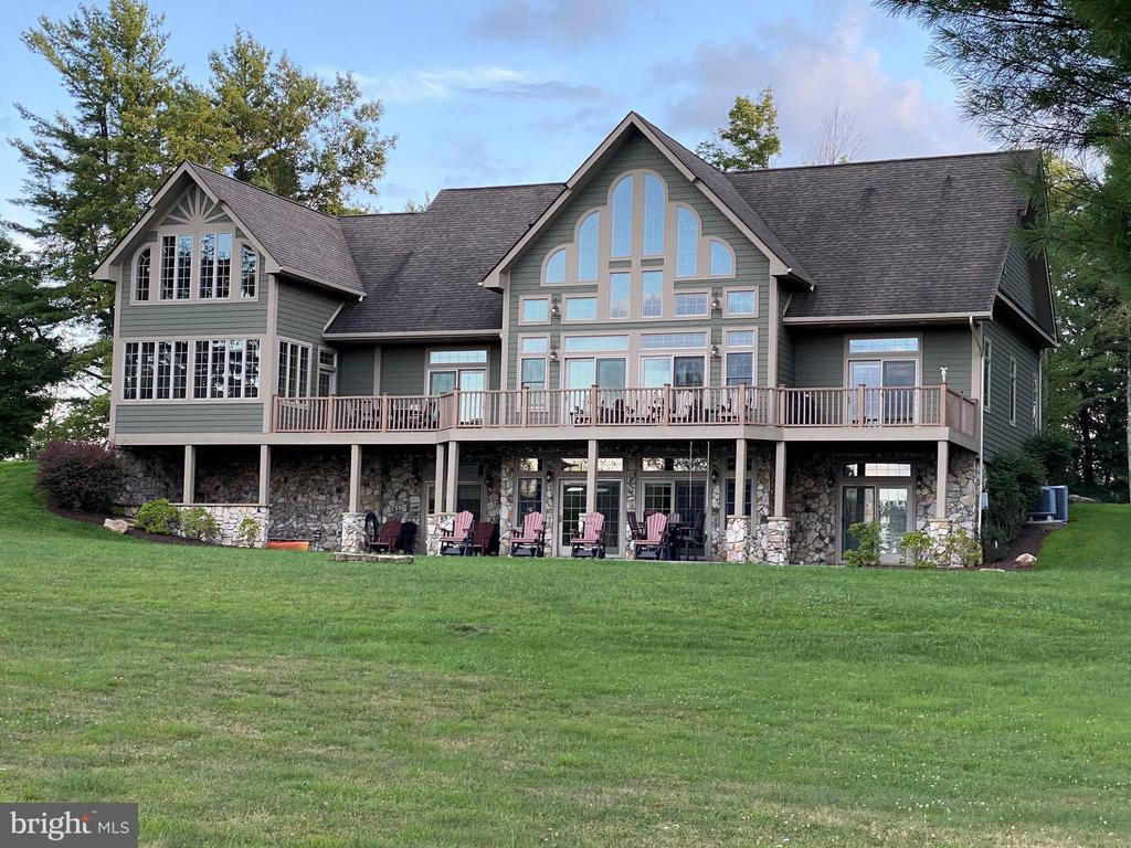 The Reserve at Holy Cross occupies its own peninsula of lakefront and lake access homes that enjoys the privacy of a non-rental community through its covenants.   LOCATION is remarkable.   Only 5.7 miles to the Arrowhead area on US 219 - easy commute to resort amenities, restaurants, conveniences and in 11  minutes,  return back home to a serene and private retreat.  Seasonal Views.  Very close by is your access to (2)  deeded dock slips.  The waterfront location is great for swimming, canoe / kayaks, fishing and just simply enjoying Deep Creek Lake.  Indoors,  gathering in the great room and gourmet cooking in a 15 x 15 kitchen is delightful.  With 5,200 +/- of finished living space,  home has 3 Au Suites.  The first one is on the Main Level that promotes one floor living.  There is a washer dryer on this level along with the 2 Car Garage,  Kitchen, Living Room, Dining, Foyer with sliding doors to an expansive deck that connects to an outdoor screened porch (furnished for lounging & relaxation). The 2nd Au Suite has the entire floor of the Upper Level:  with its own Living Room in the Loft (fabulous views),  and a very large bedroom that has French doors that open to a private sitting area with flexible use.  This area is supported by its own Rinnai Tankless water heater.   Check out the photos to view the extra large private bathroom.  The Lower Level has the 3rd Au Suite with 2 additional bedrooms with a shared bath.  In the center is a 24 x 22 Game Room (with 2nd fireplace) and wet bar.   2nd set of Washer and Dryer on this level.   All  3 Au Suites have very large bathrooms with a separate Shower and Bathtub.  ENJOY the Radiant Heat Floors.   Deep Creek Lake enjoys an elevation of 2900 +/- ft above sea level.  Evening bonfires are undisturbed by bugs that prefer humid weather.   This Four Season Lake is special.  Whether it be living indoors or outdoors in this special place you can call home,  it is truly perfect for a second home and year-round living.