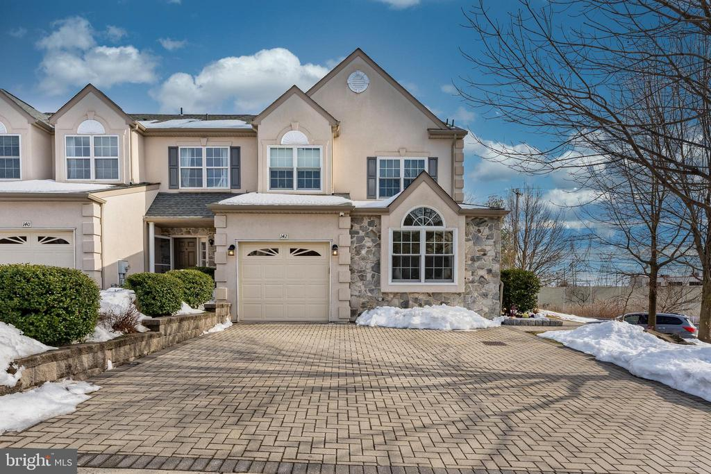 "Welcome home to 142 Ashley Way in highly desired Oakwood at Plymouth. Located in Colonial School district, this spectacular,4 bedroom, 3 full, 2 half bathroom. 4,679 square foot end-unit home is the ultimate in town home living. Prepare to be impressed the moment you open the front door; pride of ownership and quality workmanship are undeniable. A covered porch leads you into a bright foyer and that opens to a spacious living room where a gas fireplace with custom built-in bookshelves is the focal point of the room. The room also features gorgeous, wide plank, hardwood floors and detailed millwork that can be found throughout the home. The living room flows seamlessly into the dining area and onto the kitchen. The sun-filled dining room includes a bay window with custom seating, built-in cubbies and access to the expansive covered porch. The gourmet kitchen boasts granite counters, tile backsplash, a farm sink, center island with pendant lighting, Viking 36"" gas range with hood, wall oven, desk area, crown molding, and more. A study/playroom can be accessed through glass French doors and offers vaulted ceilings, bay window with custom cushions and recessed lighting. A powder room completes the first floor. The well positioned staircase leads you to the second floor, but don't miss the built-in storage box at the base of the stairs. It is easy to see that no detail was overlooked. On the second floor double doors provide an entrance into the grand, primary bedroom. Enjoy hardwood floors, gas fireplace, chair rail and crown molding, ceiling fan, walk-in closet with California Closet system, and a fabulous niche with minibar offering a small refrigerator, sink, and additional storage. The luxurious, en-suite is fit for a king or queen. A jetted tub, double vanity, tile flooring,and a spectacular brand new walk-in shower with marble tile surround and frameless glass door provide a spa-like experience. There are two additional bedrooms on this level each offering plenty of closet space, hardwood floors, ceiling fan, recessed lighting and more. The two rooms share a full hall bathroom with tub/shower combo. Laundry is conveniently located on the 2nd floor as well. On the third floor is an office space with custom built-in desk and storage. This space is ideal for an in-home office or study area. Opposite the office are double doors leading into the 4th bedroom. The incredibly spacious room offers hardwood floors, vaulted ceiling, walk-in closet, and a private en-suite bathroom. The third floor could also work well as an in-law suite or room for an au-pair. The full, finished lower level offers even more functional living space and is perfect for entertaining. The expansive bar area includes a large wet bar with plenty of seating-there's even a dishwasher, glass cabinets and a 100+ bottle wine fridge. An in-home gym has top of the line Encor athletic flooring and a third fireplace. A 2nd kitchen with range, refrigerator and storage is opposite the gym. A half bathroom is here too. Back up on the main level don't miss the amazing covered porch. Just imagine stepping out to your patio with two ceiling fans and Sonos speakers. This is the perfect spot grilling, and dining al fresco, or just relaxing. This is the only home in the entire development with an expansive covered patio. Other features include a whole house Sonos Surround System, alarm system, holiday light package, Nest thermostat, new heater with 10 year warranty (2021), new windows (2021) new exterior (2021), brick paver driveway. Fabulous location with easy access to 476, Pennsylvania Turnpike, 76, Plymouth Meeting Mall, shopping, and dining."