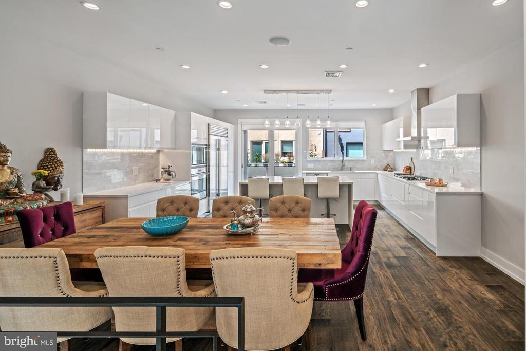 Presenting 1333 Bainbridge St, a stunning 5 bed, 3.5 bath home located in the private gated Kater Court community. Highlights of this 2 year old, like-new home include five private outdoor spaces- two roof decks & three balconies, 2-Car garage parking, a 7-stop elevator, over 4,200 square feet of living space, and 8.5 years of Tax Abatement remaining. Enter into the main sitting room featuring wide-plank hardwood floors that continue throughout the home and a stunning fireplace spanning from the floor to the 16' ceilings. Continue up to the open concept kitchen and dining room where you'll find top of the line Sub Zero and Wolf appliances, custom European cabinets, an oversized waterfall island, under cabinet lighting, and access to the first of five outdoor spaces. Up the floating stairs with 3-inch oak treads you'll find two spacious bedrooms each with walk-in closets and one with a private balcony. A tasteful hall bath with dual vanities and convenient upper-floor laundry complete the second level. The third floor Owner's Suite boasts a tranquil master bath, private Juliet balcony, and a fourth bedroom that has been converted into an enormous walk-in Wardrobe closet. An additional full bath on this level is convenient to the roof decks and fourth floor living space. This flex space offers the perfect place for entertaining, a home office, or sun-filled yoga studio. Take the elevator back down to the lower level where you'll find a fully finished basement with 12' ceilings, a second fireplace, and a separate den. Additional features of this incredible home include 8.5 foot solid core doors throughout, surround sound built-in on all levels, dual-zone Nest thermostats, and a Ring doorbell. Right in the heart of Center City, this property is located steps from South Street and within walking distance of Rittenhouse Square, Queen Village, and all of your favorite hot spots in the city. Make an appointment today because this home is sure to wow you!