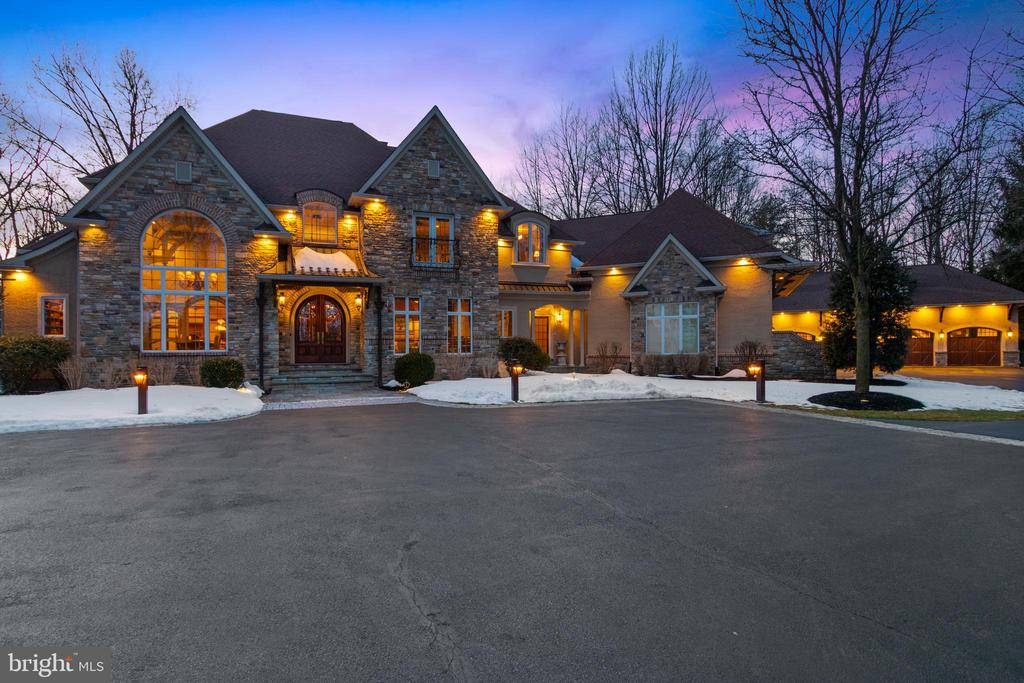 This stunning, custom built Gigliotti stone manor home is truly exquisite.  Located in coveted Lower Gwynedd, this home is situated on a private park-like 2.4 acre lot with mature landscaping and private drive off a formal entry. As you enter through the stunning arched doorway, you are greeted by 14 to 19 foot ceilings and gleaming hardwood floors throughout the 1st floor.  This meticulously maintained home offers 5 bedrooms, 5 full baths, 2 powder rooms, an expansive gourmet kitchen, fully appointed office, banquet sized dining room with impressive architectural gables and built in floor to ceiling storage cabinets, and the center of this stunning home features an impressive living room with gas fireplace, custom built in bar and bookcases, one of a kind millwork, with floor to ceiling windows.   Continuing through the beautiful breakfast room is a chef's dream kitchen that features an oversized granite island, 42 inch cabinets,  under cabinet lighting, Wolf double wall ovens, Dacor 6  burner gas cooktop, 2 Asko dishwashers, a Subzero refrigerator/freezer, with another Sub-Zero double drawer fridge in the island, 2 Dacor warming drawers, a beverage cooler, with an additional fridge and separate full freezer in pantry completes this dream kitchen! As you walk through this  spectacular home, the 1st floor spacious master suite has a separate sitting room with a built-in desk area, sizable his and hers closets with custom built-in dressers and shelving, and a sumptuous master bath with a whirlpool tub, multi-head oversize shower, radiant heat flooring, and an expansive amount of cabinets and counter space including his and hers vanities and makeup area. Upstairs you will find an impressive 900 sq ft private junior suite with oversize walk-in closet, ensuite elegant bathroom with radiant floor heat, and attached lounge room with skylights. Finishing off the 2nd floor is an additional 3 bedrooms, one is ensuite, the other two share Jack and Jill bathroom. The 2nd floor offers plenty of room to spread out. The finished basement offers unlimited possibilities with a double french door exit with walk-up to backyard, full bathroom, 9 ft ceilings throughout, an expansive main room, an equally expansive separate room which could be used for exercise room, home theatre, etc.  Includes plenty of unfinished storage space as well. The attached three car garage boast deep bays with individual 9 ft wide doors, and professionally applied epoxy coated floor. An impressive detached four plus car garage was built in 2015. Over 1500 sq ft of space with impressive lighting, 14 ft ceilings designed for car lifts for the enthusiast, and a large loft for storage. Ample parking in the courtyard and driveway for an additional 20 plus cars. The private parklike backyard offers a Dacor built in grill and warming drawer in a custom stone work area, 2 flagstone patios, mature trees and endless possibilities. Some extra special features that are  included in this beautifully appointed 8600 plus sq ft home are a 4 zone HVAC system, 12 zone house music system, and Culligan water softener to help seamlessly manage this impeccable property.  Also includes a Generac natural gas generator, Anderson windows, rough in elevator shaft, and lawn irrigation.  Security needs are covered by a comprehensive indoor/outdoor 32 camera, alarm, fire, and flood monitored system. A TRUELY MUST SEE PROPERTY!