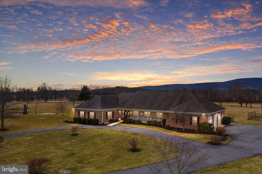 Every once in a while, a very special property becomes available.  This is one of those homes.  Original owners built this custom home with unsurpassed quality in mind.  Nestled on 17 gorgeous acres with absolutely stunning views.  Desirable and hard to find main level living captures all you need for everyday life on one level.  Gorgeous large living room with cathedral ceilings, hardwood floors and brick wood burning fireplace.  Separate formal dining room with wood floors.  Very large family room with stone wood burning fireplace and wet bar.  Exceptional views from this room that leads to a screen porch with custom sectioned screen for wind protection.  Bright kitchen with abundant cabinet space, island and desk area.  Upgraded appliances include double ovens and cooktop.  Main level primary suite with more gorgeous views, walk in closet, double sinks, soaking tub and separate shower.  Three more main level big bedrooms.  Nice wide hallways with lots of storage.  Lower level offers complete living quarters perfect for in-law or au/pair.  Full kitchen, family room with a 3rd wood burning fireplace, and a den area with walk out to patio.  Additional area with emergency exit window access and closet.  Three plus car garage, each with remote and an additional work shop space.  Back-up generator with automatic cut-over services to major components.  Two wells and hot water heater has recirculation unit.  Large 14X33 ft storage shed with electric and water.  25X65 ft. garden area with landscape boarder, two trellises, two raised planters & established herb garden.  Nice fenced rear pet area with ramp for dogs.  Alarm system monitors all windows, doors with active sensors and intercom.  This hard to find large parcel of land is perfect for animals, gardening, hay...   This is home, land and sunsets is one not to be missed!  BE SURE AND CHECK OUT THE I-GUIDE TOUR.