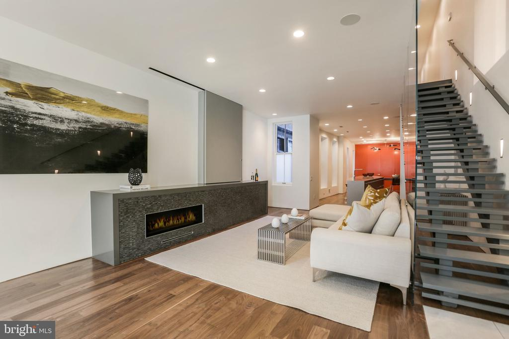 New Price - A stunning contemporary design from award winning architect, Robert Gurney. This West End/Dupont Circle home won Gurney the A1A Design Award. The main level offers, Brazilian walnut flooring, high ceilings, a gas fireplace, and a special sliding compartment for your flat screen television. There's a seamless flow from the living room into the eat-in kitchen. A massive center island is perfect for entertaining or family dinners.  Enjoy Miele kitchen appliances, and a wine refrigerator.  The formal dining table is connected to the kitchen. A nearby half bathroom and coat closet are hidden behind the rear accent wall. Heading upstairs, you'll love the glass and steel staircase. It's one of the treasures of this home. Gurney carefully designed this home to welcome sunlight from all over. Large windows, skylights, and even a see-through glass staircase platform allows each room to fill with warm light.  Enjoy a beautiful primary suite, walk-in closet, and bathroom. Two more bedrooms, and a laundry room are on the second level,  The top level offers another full office suite or guest bedroom, and en-suite bathroom. The nearby entertainment room was designed with custom built shelving and a Murphy bed for additional guests.  Ceiling mounted audio speakers are connected to a Sonos music system. This  is the perfect time of year to enjoy two outdoor spaces.  One deck is located just off the kitchen, above the garage. A wonderful place for outdoor family meals. The rooftop deck offers breathtaking views with a gas burning fireplace. Two covered parking spaces in the rear.  The lower level apartment comes with a certificate of occupancy. Tenants are currently month-to-month, but are willing to extend their stay if buyer agrees.  Previous rental income: $3,600 a month. Square foot measurements of the home are approximate.