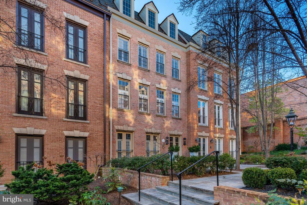 1820 Kalorama Square NW is distinguished in stature and impressive in presentation. Beautifully designed and tailored to fit the modern lifestyle, this five-level all-brick townhome in the gated community of Kalorama Square is steeped in impeccable finishes, hand-picked stone selections, and a floor plan made for large scale entertaining. With 5 Bedroom Suites and 5.5 Baths, this prominent residence spans approximately 4,500 finished square feet and is adorned with a number of comforts including an Elevator that services all 5 levels, an attached 2-Car Garage, a dedicated level for the vast Primary Suite, and an expansive private Patio. Through a well-manicured promenade and past the neighboring homes is 1820 Kalorama Square NW. The Main Level welcomes you with a wide and gracious Foyer with an elegant staircase that is lined with an imported wool sisal stair runner. The incredible Gourmet Kitchen is dressed in white quartz and features a Wolf steam oven, Wolf wall oven, Bosch dishwasher, Wolf 5-burner induction cooktop, pot filler, and a Sharp microwave drawer. Flanking either side of the Kitchen are both dining areas, including a charming Breakfast Room and a spacious Dining Room that opens to the rear Patio.   The Second Level is made up of the Living Room and Den, both warmed with beautiful fireplaces, custom millwork, and large windows. There is a lovely Wet Bar off the Living Room along with a Powder Room.   The Third Level is dedicated to the Primary Suite and lives comfortably with a Bedroom, two owner Baths, and a huge Dressing Room with a built-in wardrobe. The Dressing Room may be easily transformed into an additional Bedroom or an Office. There are two Bedroom Suites on the Upper Level, each with their own private Bath.   The Lower Level is a functional and well-designed space that boasts an Au Pair or Housekeeper's Suite, a Laundry Room, a Full Bath, and access to the 2-Car Garage. The Au Pair/Housekeeper's Suite is spacious and thoughtful, with a Bedroom and connecting Sitting Room.  Kalorama Square is located at the corner of Phelps Place NW and S Street NW in the esteemed neighborhood of Kalorama. This private and gated community consists of merely 25 townhomes and offers an autonomous enclave that is meticulously maintained and is accompanied by a number of desirable amenities. Residents enjoy the swimming pool, 24/7 security, landscaping and private 2-car garages. Sited on the former Holton-Arms School Gym and playing field, these townhomes were built in the mid-1970's and have been wonderfully cared for. In addition to the wonderful amenities of this special community, Kalorama Square is also adjacent to Mitchell Park and across the street to the Spanish Steps. Bounded by the Massachusetts Ave NW and Connecticut Avenue NW corridors, there are a number of Embassies, restaurants, and cultural experiences that surround this lovely neighborhood.