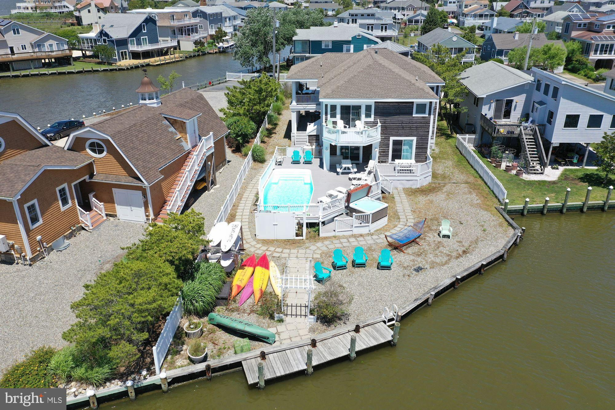 Great investment opportunity to own a direct waterfront home in the heart of Fenwick Island!  Guests enjoy stunning bay views from almost every room in the home, a private boat dock to accommodate multiple watercraft, kayak storage, an outdoor shower, a hot tub and a personal swimming pool with an expansive Trex deck providing a perfect place to sunbathe, entertain and take in gorgeous sunsets everyday.  The main level of this coastal gem features warm hardwood floors, vaulted beamed ceilings, a spacious gourmet kitchen with granite countertops, stainless steel appliances and an expansive center island.  An open floor plan encompasses a family and dining room with double-sided gas fireplace.  Sitting area adorned by sun-filled windows and sliding doors leading to a generously sized wrap around balcony partially covered for extended dining options.   A balcony off the primary bedroom suite allows you to take in all the property has to offer and is complete with an oversized tiled shower stall with glass doors, dual vanity and clawfoot tub.  Lower level offers a laundry area, four bedrooms, three en-suite, and a bonus room that can be used as a sixth bedroom with a wet bar and sliding door access to the pool.  Located at the end of a quiet street it is an easy walk to restaurants, boutique shopping, mini-golf and many other Fenwick fun spots.  House is being sold completely furnished.  Current rental bookings total more than $200,000 in revenue!