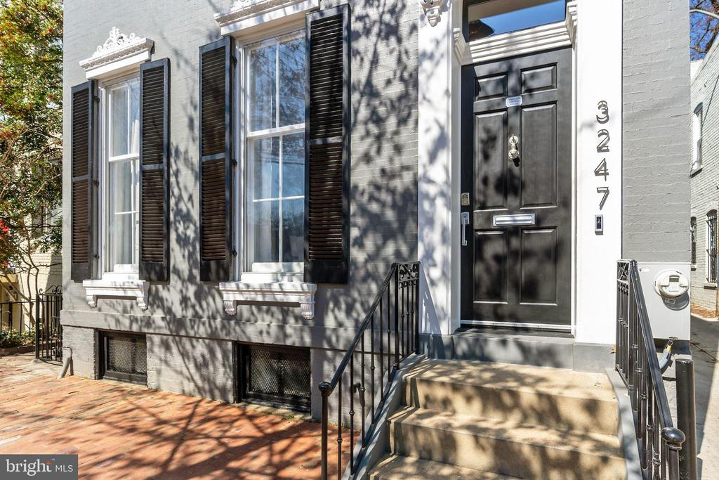 New Georgetown Listing! A stunning contemporary, 3-level, creatively renovated historic home with 2-car parking, nestled along a tree-lined, cobblestone street in DC's iconic Georgetown neighborhood. This elegant, one-of-a-kind four bedroom, three and a half bath masterpiece, has clean lines, modern finishes, serene colors and an open floor plan, appealing to the eye at every turn. The main level features a spacious sun-lit living room with 9' front windows, a stone accent wall, built-in entertainment center and gas fireplace. The dining room opens into an exquisitely appointed chef's gourmet kitchen with Miele appliances, custom Ralph Lauren pendant lights, and contemporary stone island perfect for meal prep and entertaining. Located off the brightly-lit kitchen is an expansive, beautiful two-tiered patio and terrace with comfortable outdoor seating and built-in BBQ, ideal for intimate dinners, large parties and alfresco entertaining.  A floating staircase and exposed brick wall lead to the upper level, featuring a primary suite with a custom-built walk-in closet and en-suite bath, two additional bedrooms, office, and laundry area. The lower level lends itself as a family room or fourth bedroom/guest suite complete with full bath and walk-in closet. This is a unique property, located amongst picturesque historic brick homes, fashion and design shops, and upmarket restaurants and cafes.  Features: Custom closet system with Sliding Door Company imported glass, under-bench storage and walk-in closet with custom cabinetry; All closets with custom closet systems plus office with custom cabinetry; Custom live edge countertop in powder room and custom shelving in living room from reclaimed wood; Primary bathroom and powder room with Waterworks fixtures; Laundry center with built-in ironing board and storage; Fully integrated security system, Nest heating/cooling, Control4 sound and media system with speakers in all rooms including primary bathroom; Durable full metal seal