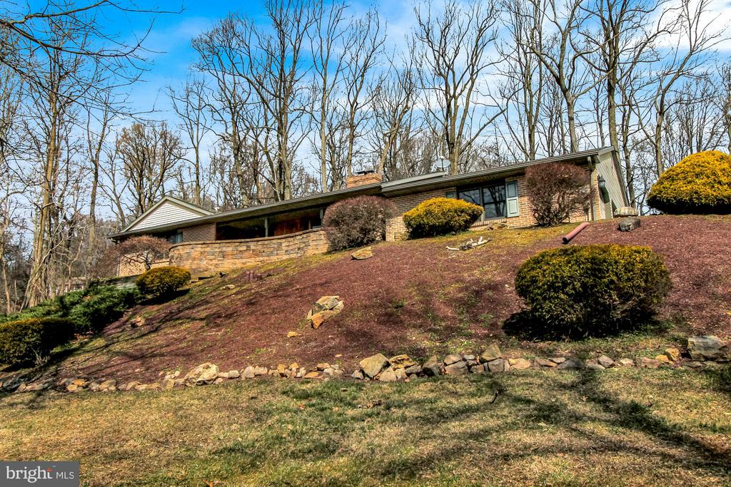 Welcome to 70 Koch Road situated on 2.96 private acres in Boyertown! This is the home you have been waiting for!  As you pull up the driveway you will be immediately impressed by the beautiful setting and breathtaking views of the surrounding bucolic hills and forests, and you will love the fantastic paver patio with an architectural seating wall to take it all in! Entering the home through the wide tiled foyer, you will be greeted by a large formal living room with Brazilian Cherry floors and a brick wood-burning fireplace with a big bay window to continue enjoying the amazing views. Straight ahead you will find the dining area and gorgeous gourmet kitchen that has been fully customized with extraordinary attention to detail including custom maple wood stained and glazed cabinets, granite countertops, 4-seat breakfast bar, stainless steel appliances, farmhouse sink, six-burner Viking propane stove-top and double oven, professional grade remote-controlled stainless steel exhaust hood, skylight, recessed lights, and a wine bar with mini fridge and bar sink! This is truly a dream kitchen! Also on the main floor you will find a welcoming family room with plenty of space to relax and enjoy; 3 nicely-sized bedrooms, 2 full bathrooms and a half bathroom including a lovely master bedroom suite with upgraded flooring and large stall shower; as well as a convenient first floor laundry room with cabinetry. Downstairs is another world all to its own, with a spacious living area including walk-out glass double doors to let in lots of natural light, recessed lighting, 2 private bedrooms, another updated half bathroom, and a bonus storage/wine room and walk-in closet. This great area could also easily be converted into the perfect in-law suite! And if that wasn't enough, this great home boasts a total of four garage spaces! The 2-car attached garage is clean as a whistle with a painted floor, and the 2-car detached garage has enough space for all of your extra vehicles or toys an