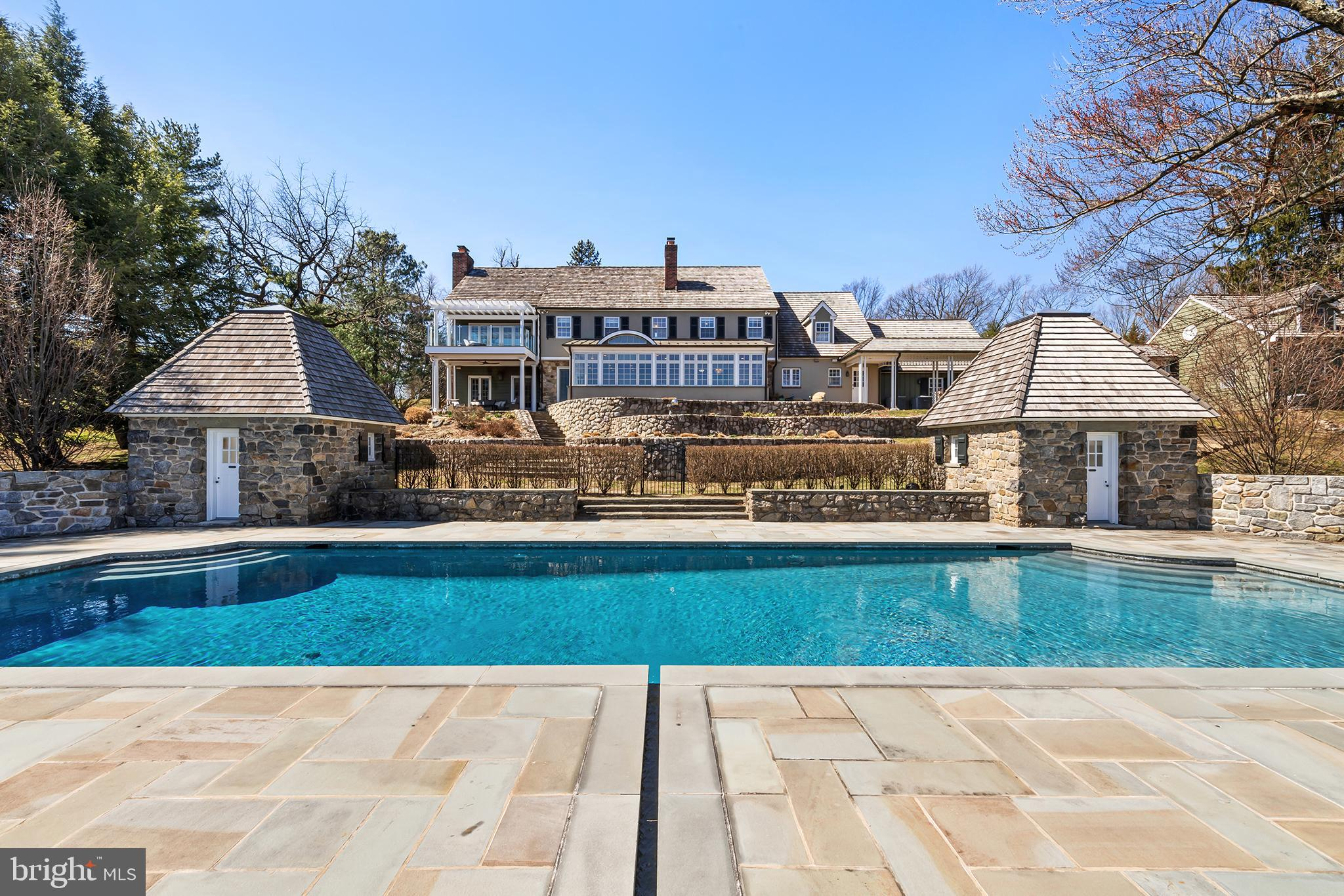 Set on a quiet cul de sac in Gladwyne, this stately five bedroom colonial offers expansive grounds and upgrades of the highest quality. Sprawling across 2.8 acres of land, 1035 Sentry Lane is complete with a renovated outdoor pool and pool house, two balanced stone cabanas that are from the original estate, several tiered gardens, panoramic vistas and resplendent sunrises that you'll never grow tired of.  Enter into a grand foyer showcasing a marble entryway, butterfly staircase, volume ceilings and a skylight window with open beams. There is a light-filled great room surrounded by walls of oversized windows overlooking the home's professionally landscaped acreage. Ideal for entertaining, the open-concept great room flows perfectly into a beautiful breakfast room and chef's kitchen. The designer kitchen boasts custom two-toned cabinetry, a quartz seated center island, two Sub Zero refrigerators, Marvel wine chiller, a Bosch dishwasher, a Bosch double oven, Wolf induction range and stainless steel hood surrounded by an ornate archway. Just off of the kitchen, there is a formal dining room, mud-room and home-office with built-ins. Additional first floor highlights include access to the attached two-car garage, two powder rooms and a large living room offering a wood burning fireplace and french doors that open to one of the tiered stone raised terraces.  Escape every evening into the lavish primary suite that is located on the second floor. This magnificent bedroom enjoys french doors that open to a terrace with glass railings affording unobstructed views, a fireplace, tray ceiling and a custom-fitted walk-in closet complemented by two wall closets. The marble-appointed primary bath has double vanities, a seamless enclosed stall shower, radiant heated flooring and a private commode with etched glass.   All of the guest bedrooms feature excellent closet space. Bedrooms 2 & 3 enjoy ensuite bathrooms, while bedrooms 4 & 5 share a jack-n-jill bath. Enjoy added recreation space thanks to the fully-finished lower level showcasing a mirrored gym with impact floor and sauna, billiard room, built-in bar, outdoor access and full bath. Sitting above the detached three-car garage, your friends and family will enjoy the spacious and private guest suite complete with a kitchenette. Alternatively, this space is perfectly suited to be an office away from the office.  The 5 car garages afford ample parking space for all your cars.  This residence has everything you could want plus more!  Adjacent to Sid Thayer Trail and Riverbend Environmental Center, 1035 Sentry Lane is located in a highly coveted section of Gladwyne. Easy access to Center City, excellent schools, lovely parks, golf courses and clubs.