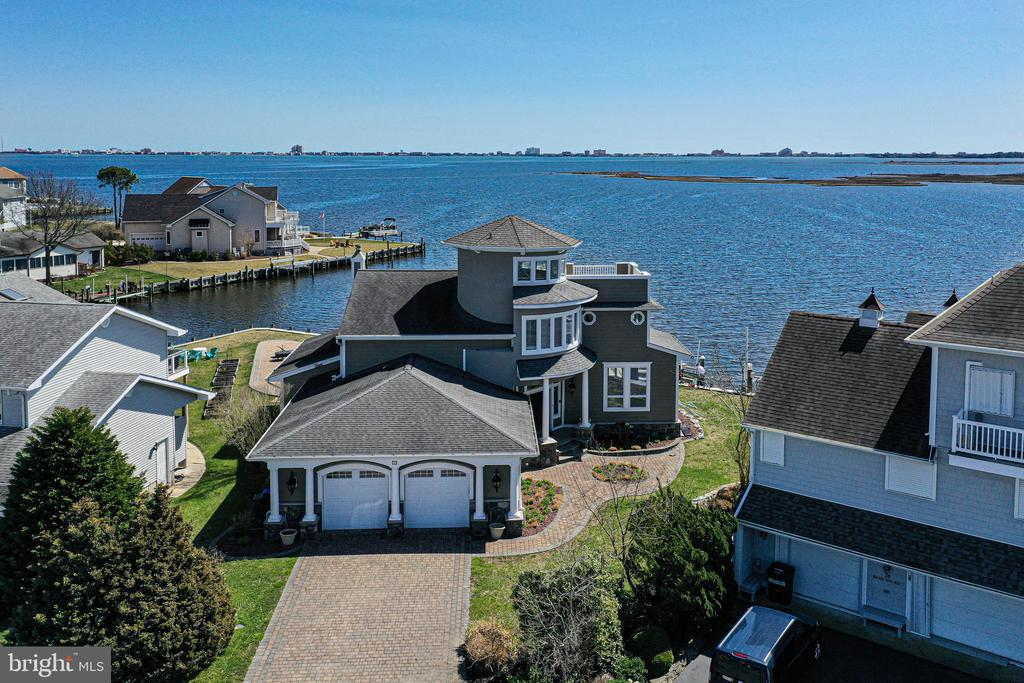 Open the door to breathtaking bay views and Ocean City Skyline.  One of 13 Point lots in Ocean Pines w/panoramic water views from every room. This one-of-a-kind contemporary California style home is in Ocean Pines, on the Isle of Wight bay, looking five miles across the water at the beautiful skyline of Ocean City.  This home is perfect for entertaining, indoors and outdoors.  Renovation in 2005-2007, this home has it all.  Gourmet Kitchen with spectacular views, includes granite counters, custom cabinets, Viking stove and stainless-steel appliances.  Formal living room and dining room.  Spacious family room with wet bar, that leads to the beautiful hardscape patio. It features 4 Bedrooms, 3.5 baths, two master suites on first and second levels. Third floor has a lovely Turret/Widows Watch which over looks the entire bay.   Outside deck off the turret. 200+/- Ft of Bulkhead with room for all of you your water sports toys.  Includes a 12,500 lb boat lift with extra-large dock and Jet ski lift.  You must see this beautiful Home.