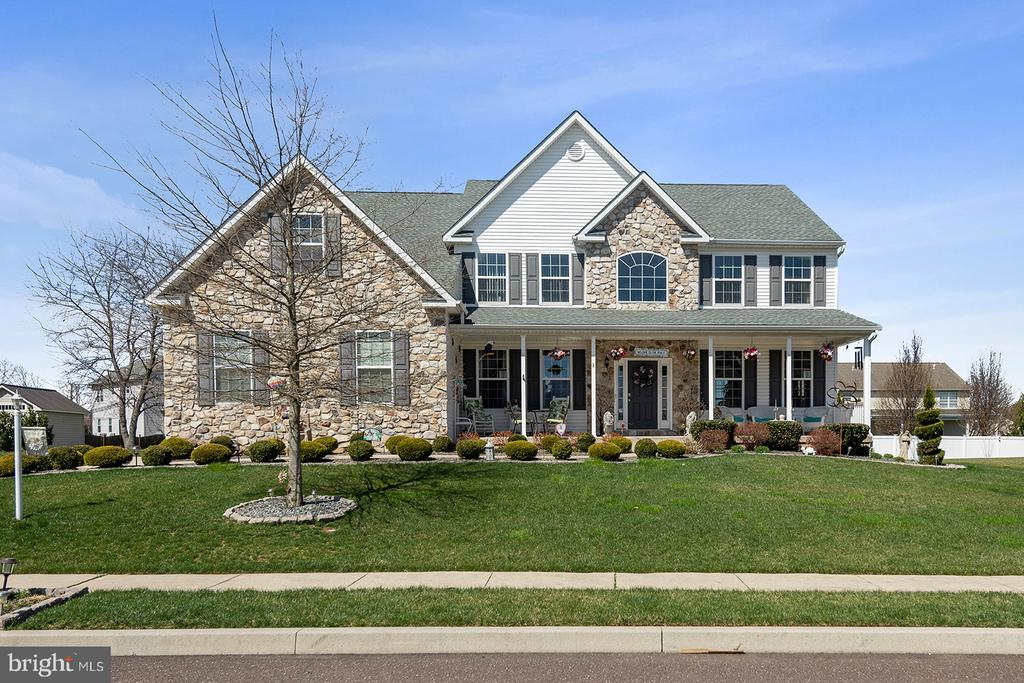 Welcome home to this STUNNING 4-bedroom, 2.2-bathroom center hall Colonial in Upper Providence Township! One of the biggest homes in the neighborhood at over 5000 SF of finished space, this beauty was built to impress in 2012. Tons of natural light from the ample windows in this home. Long porch greets you as you approach the front door. From the entry foyer with a beautiful chandelier (that lowers for cleaning ease), you'll find the sunny living room, which leads to the formal dining room, featuring beautiful hardwood flooring, chair rail, and crown molding. Through to the large eat-in kitchen, which includes granite countertops, new appliances, island with breakfast bar, beverage counter, room for a dining table, and sliders to the rear decorative stone patio and yard. Adjoining the kitchen is the spacious and bright family room with natural gas fireplace for cozy warm evenings. You'll also find a huge walk-in pantry, powder room, and access to the garage. This floor also includes a bonus room perfect for an office space or den. Head upstairs to find an incredible owner's suite with gorgeous hardwood floors, tons of windows, ceiling fan, sitting/dressing area, dual walk-in closets, and ensuite bath featuring separate stall shower and soaking tub, and enormous vanity with dual sinks. Down the hall, you'll find 3 additional carpeted bedrooms, a hall linen closet, full hall bath with tub shower, and laundry room with built-in cabinetry and pull-down stairs to the attic. The full basement is completely finished with carpet and recessed lighting, and includes a half-bath, extra large storage room and a separate storage closet, radon mitigation system, sump pump with backup battery, and sliding door to the walkout stairs leading to the backyard. The home also includes a large concrete driveway and attached 2-car garage with electric opener. The home has dual zone high-efficiency heating and cooling with a brand new basement heater unit as well as a high-efficiency hot w