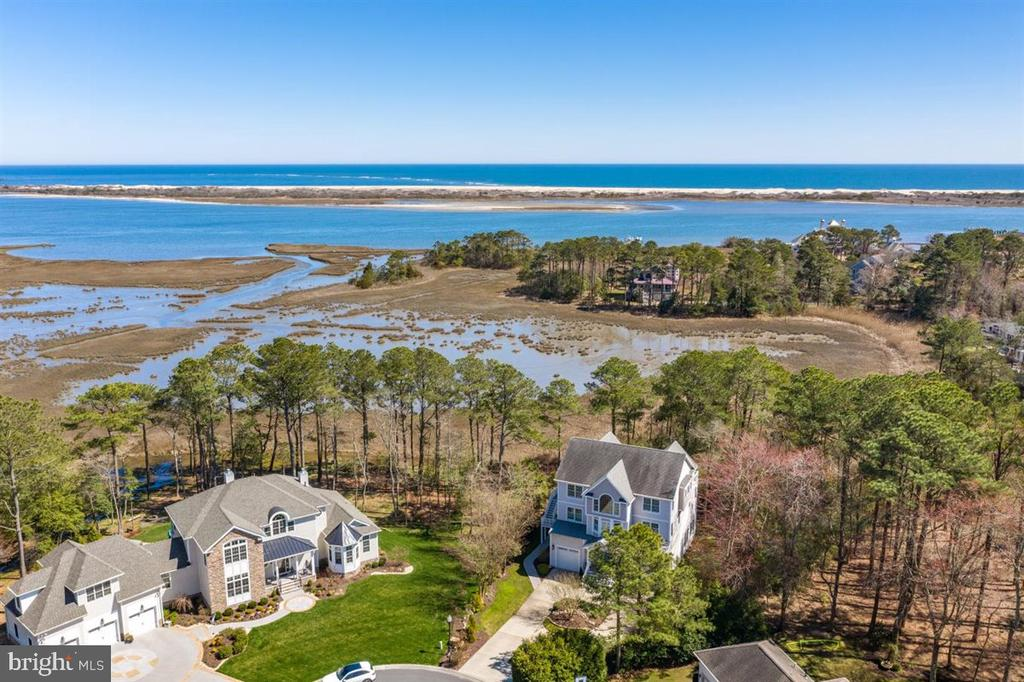 Coastal elegance meets fantastic views of the bay and Assateague. This stunning home was well thought out with an open-concept floor plan, wall-to-wall windows capturing endless views of the bay and Assateague (and even a peek of the ocean), flowing hardwood floors, a gourmet kitchen, and a spacious family room with custom built-ins with natural gas fireplace. Soak in the sun and the sound of the ocean waves on the main level deck, and watch the Ocean City pier light up at night. The master suite is located on the main level with great views of the wetlands and bay, his-and-her closets, and a grand master bath with a jacuzzi tub and tile shower. On the top level you'll find the perfect space for a home office with a beautiful picture window overlooking the neighborhood, a lounge area to relax and watch TV, four spacious bedrooms with easy bath access, and a sunny deck with unbelievable views of the bay, Assateague, and the ocean. The ground level offers an oversized 3-season room with access to a large sundeck. While this home doesn't currently have an elevator, there is an elevator shaft already installed, making elevator installation fairly simple. You won't find a better location, being on a cul-de-sac and no neighbors behind you to block your view and giving the perfect private setting. Ocean Reef is a prestigious community located just 4 miles to the beaches of Ocean City, 2 miles to Sunset Marina for boating fun, 2 miles to popular local restaurants, 7.5 miles to charming Berlin, and 2 miles to popular golf courses.  Ocean Reef homeowners can also purchase a pool membership at the neighboring community, Mystic Harbor. With so many special features in this home, be sure to ask for the Property Features List!