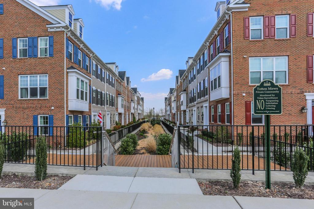 Welcome to 605 Totten Mews NE! This stunning townhome, built in 2017, features three full levels of living with three primary bedroom suites (one on the first floor and the additional two on the third floor) and a half bathroom on the second level. From the community courtyard, you enter the front door to the first level. Here you will find your first bedroom suite  and interior access to your rear entrance, one-car garage. Heading up the stairs to the second level brings you into a light-filled common living space with an open concept kitchen, dining, and living room. Sky-high ceilings, crown molding, gorgeous courtyard-facing windows, and a stunning kitchen with stainless steel appliances, a central work island, a butler's pantry, and a dry-goods pantry with French doors. Access to your rear balcony is just off of the kitchen. Upstairs you will find your additional two bedroom suites, a linen closet, and your laundry room with French doors. The rear bedroom is your primary bedroom suite with a walk-in closet and an ensuite bath with double sinks and a glass-encased shower. As the only owners of this home, the sellers opted to upgrade the builder's standard features seen throughout this community, including custom closet systems, light fixtures, a kitchen backsplash, window treatments, washer and dryer, carpet in the upstairs bedrooms, hardwood floors, and garage shelving. Residents of Totten Mews enjoy Totten Mews a private tot lot playground for the community and ample green space for kids and dogs. Located only a short distance from the Fort Totten Metro (red, yellow, and green lines) and the Fort Circle Parks.