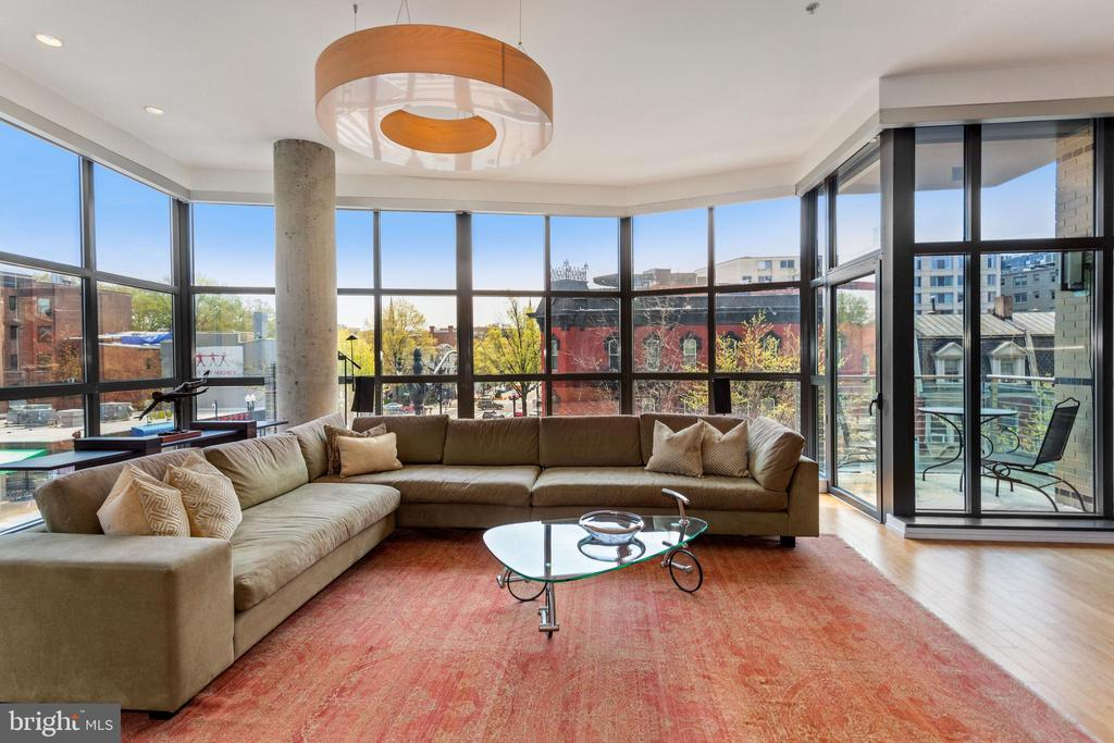 Set in the epicenter of Logan Circle and the 14th Street Corridor, this dramatic two bedroom, two and a half bath plus dining room/den corner flat with two balconies, two car garage parking, in unit washer and dryer and extra storage is a few blocks to downtown, across the street from Whole Foods, and surrounded by a host of retailers, restaurants, coffee houses, art galleries, furniture stores, live theater and nightlife venues, fitness and conveniences. Floor to ceiling industrial style windows with remote control shades provide a bird's eye view of beautiful cityscape from every room and gorgeous hardwood floors, eleven foot ceilings, exposed brick, built in audio, and custom art lighting are featured throughout the expansive, open and light filled living area with a fireplace and built-ins, European gourmet kitchen with Scavolini cabinets, granite counters, professional stainless appliances, gas cooking, a wall oven and Italian glass backsplash, a master suite with a walk in closet and lavish marble and limestone tiled bath with double vanities, and a second bedroom suite.